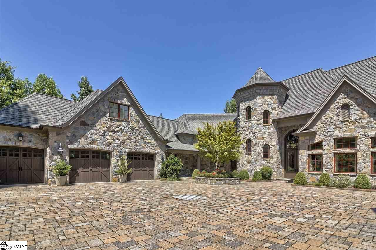 Sitting at the end of a tree lined tumbled cobblestone drive, beyond the mahogany gate, this property sits within a setting that is at once impressive and tasteful.  A solid stone facade with a turret housing an interior custom staircase and two wings, each with three car garages, envelopes the visitor in a comfortable yet sizeable motor court area.  Welcome to 235 Jasmine Point in The Cliffs at Keowee Falls.    A bouldered, pondless waterfall projects the restful sound of falling water throughout the courtyard.  Upon entry into the residence, there is an immediate and pervading sense of quality, sophistication and style.  The eye is drawn to the great room, which rises to 25 feet, and includes a wall of Eagle windows  showcasing expansive lake and mountain views to the northeast.  The setting is one of the finest available on Lake Keowee – a point property at the apex of a large, private cove, comprising 1.12 acres with 526 ft of stained boulder shoreline.  This is the best of all worlds – expansive open water views and a quiet cove for the covered slip dock, swimming, or peaceful relaxation on a summer's eve.     The main floor of this Keith Price (Atlanta GA) designed home, constructed by Greenville's The Paragon Group, is quintessentially open, flowing and inviting.  The expansive kitchen, with center-island, pantry and custom cabinet-matching Stylecraft range hood, houses Viking, Sub Zero and Miele appliances, and lies open to the walnut lined keeping room/library, with one of five gas and one wood burning fireplaces to take the chill from early spring or late fall mornings.   The dining room is conveniently nearby, as is the great room, with its floor-to-ceiling full masonry fireplace and limestone surrounds, all of which make family gatherings and entertaining simultaneously convenient, comfortable, and conversant.   An impressive master suite with fireplace and separate sun/reading room occupies the east wing, enhanced with calming lake and mountain views.  