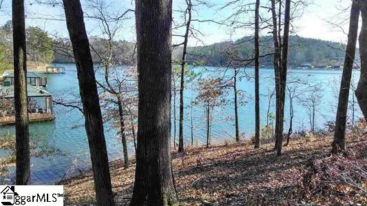 Lake Keowee Waterfront Home Site in the Gated Cliffs Community of Keowee Springs. Over an acre of property with 200+ feet of shoreline with a Covered Slip Dock in Place. Beautiful grade and elevation with mixed trees and views of the green clear waters of Keowee. Building site could offer sweeping views and is perfect for walkout basement plan.