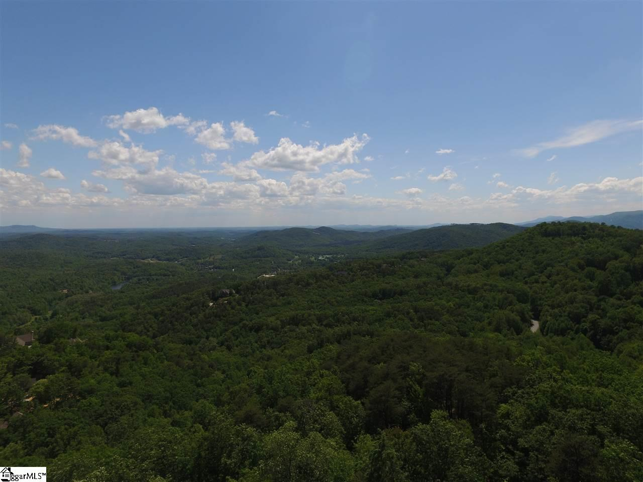 Experience 180 degree breathtaking mountain views from this privately located homesite on over 6 acres of land! Views include Table Rock, Cliffs Valley Golf Course and Clubhouse in the distance. Level build site with walk out basement best suited for site. There is a free flowing creek on the property. A Cliffs Club membership is available to purchase with the real estate giving you access to all 7 of The Cliffs Clubs.