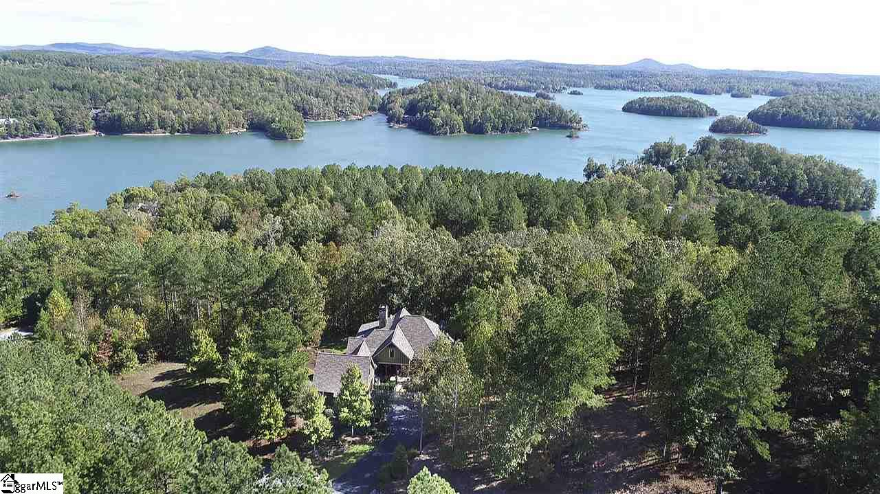 Resting in an idyllic setting of hardwoods on a largely level site that is embellished with beautiful landscaping details, this home is located just beyond a narrow woodland from Lake Keowee's crystal clear waters. Available boat slips are a short walk or golf cart ride away. Move-in ready, the lovingly maintained home embodies warmth and refinement. Its open floor plan boasts hardwoods and tile throughout, soaring ceilings with rustic wood accents, welcoming morning sun, outdoor living spaces on both levels, and both indoor and outdoor stunning, floor-to-ceiling stone fireplaces. The lovely granite kitchen, which sits adjacent to the great room's living and dining areas, features Jenn-Air appliances, a six-burner gas cooktop/range, and long-range mountain views from double windows above the sink. (Note that additional mountain and lake views are displayed seasonally.) Just off the kitchen and great room is a screened porch with fireplace and grilling area. The main-level master suite includes a gorgeous free-standing, clawfoot soaking tub. The lower level entertains guests with a den/family room, game area, wet bar with beverage cooler and ice machine, three spacious guest suites, one of which is presently used as a well-appointed office, and covered patio. Intelligent design maximizes the home's 3,200 square feet and incorporates efficiencies like Icynene foam insulation, tankless hot water heater, and gas starters for the fireplaces. The home's quiet cul-de-sac is just inside The Cliffs at Keowee Falls' rear gate, so it enjoys easy access to the nearby town of Seneca, as well as Clemson University. The area is ideal for walking (the community has a comprehensive trail system), and additional acreage is optional, as the adjoining property is developer owned. The home's elegant furnishings are negotiable, and a variety of Cliffs memberships are available.