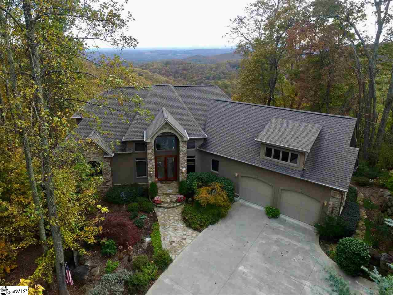 "Come home to The Cliffs at Glassy, The Cliffs' original gated golf and wellness community atop Glassy Mountain in Landrum, SC. Prepare to be amazed by this meticulously maintained contemporary mountain retreat where no detail was spared. Built on 3.55 acres with a magnificent waterfall across the street, producing a running creek behind the property creating the soothing effect of running water. Offering immense privacy, Brazilian cherry wood floors, casement windows, and an open, extremely livable floor plan, 5 bedrooms, 4 full baths, 2 half-baths, a bonus room with 4 built in bunk beds. There are 4 fireplaces and panoramic views of mountains, valleys and city lights at night which can be viewed from nearly every room of this 3 story, 5,700+ sq. ft. home. The main level open floor plan provides more than enough space for entertaining friends and family. A great room with fireplace, large kitchen, dining room, breakfast area, and screened in porch with easily adjustable windows to create a year-round room. The screened in porch has a fireplace and an indoor grill, vented out, to be used even in the coldest of weather. The kitchen is custom cabinetry extending to the top of 10-foot ceilings with custom 12"" dental moldings. The master bedroom suite, also located on the main level, features a nice size sitting area with a lighted tray ceiling, television built-in closed cabinetry and a fireplace. Access the main level 22' x12' outdoor covered deck from the master suite, or the kitchen/dining area. The upper level has a landing that expands from one side of the house to the other, looking down into the main floor family room with magnificent views of the outdoors. There are 2 bedrooms suites with their own full bathrooms. Every bathroom in the home has custom tile and granite or marble with glass shower doors. In addition, there is a bunk room on the upper level, with 4 built-in bunk beds and a large living area for TV and games. The lower level of the home includes an additional recreation room with fireplace, built-in wet bar and wine. There are 2 additional bedrooms, one full bath, and one ½ bath. The two bedrooms are currently used as an office, and the other is currently a fully equipped gym. Exit the glass doors to a 65' long deck with additional views and plenty of space for entertaining large parties. Off the lower level deck, there is a large storage/potting room.  A sink is included for an ideal place to pot plants. This extraordinary mountain home has had one owner who designed the home with a unique touch to detail in every room. Landscaping is lush, with different plants that bloom year-round. A Cliffs Club membership is available to purchase with the real estate."