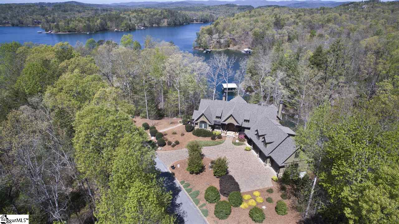 """-Five bedrooms, four full and one half bathrooms and bright, spacious living areas comprise this 5,400 sq ft waterfront home at the Cliffs at Keowee Vineyards, with good proximity to the clubhouse and golf course and a spacious 3-car garage. - Open floor plan to great room, dining area and kitchen with ease of access to screened and open porch.    - .86 acres of mixed forest and meticulous landscaping with zoned irrigation surround the low-maintenance exterior of this home.   - The desirable double slip covered boathouse has electricity available for boat lifts, if desired. - Carefully selected finishes and fixtures include specialty tiling, custom cabinets with rope detail, upgraded plumbing fixtures, including Grohe and  Hansgrohe faucets and Blanco sinks, a Jacuzzi tub and Jentle Jet laundry sink, heated bathroom floors, large walk-in cedar-lined closet and cedar sauna, stained glass windows, home gym, hot tub and oversized """"bonus"""" bedroom. - The kitchen is well-equipped with Bosch and Kitchen Aid appliances, including double convection wall ovens and warming drawer and DCS 5-burner gas range by Fisher & Paykel, with custom-built 600 CFM hood.  A walk-in closet with etched glass pantry door is both stylish and practical, boosting the natural light from a pretty octagonal window. - Four HVAC zones (two with humidifiers) ensure comfort throughout, storage is both extensive and varied, and the home is outfitted with a lightning protection system.  Control 4 home automation system allows lighting, thermostat control, two security cameras, and monitored security system. Audio and video are available in virtually every room of the house."""