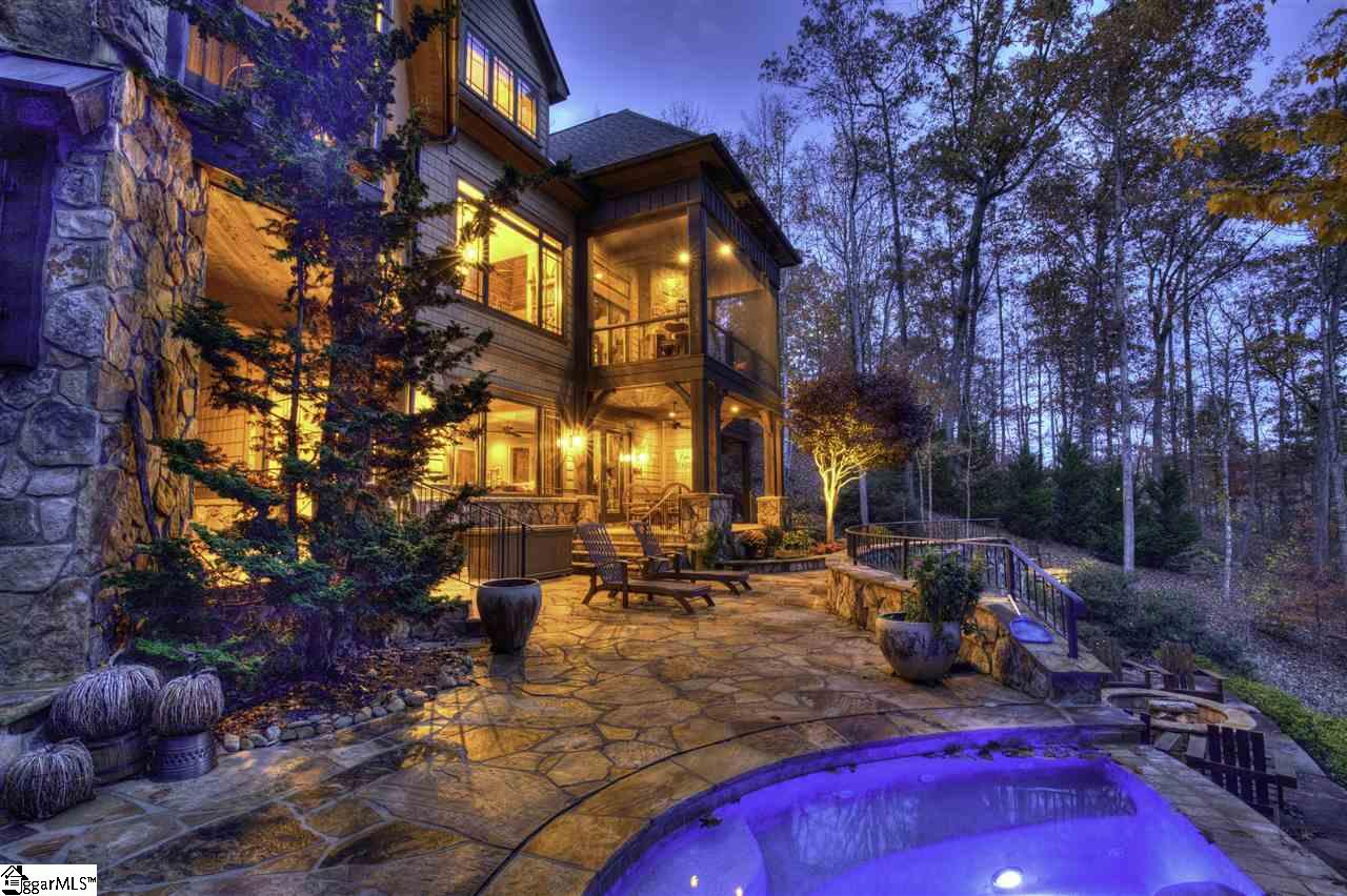 With vast lake views, exceptional craftsmanship spread across three levels, and an expanse of backyard bliss that incorporates multiple water features, an infinity hot tub, putting green, and numerous terraces that step down to Lake Keowee's clear waters, 610 Sweet Fern Trail is a not-to-be-missed gem.   Past a gated entry and at the end of a long paver drive bordered by boulder retaining walls, the home presents an impressive facade of stone and masonry siding. Double doors lead to uninterrupted lake vistas on the opposite great room wall. Calm neutrals mix with a stacked stone fireplace, plank ceiling, and built-in shelving. Folding glass doors open wide to the first of two waterfront screened porches with stone fireplace.    Built around a grand island, the kitchen is handsome and hard-working. Gourmet dreams come true with a collection of premium appliances: Dacor gas range with double ovens, Sub-Zero fridge with custom paneled doors, separate freezer drawers, paneled Miele dishwasher, dishwasher drawer, and walk-in pantry. Just off the kitchen is the home's second screened porch, again with stone fireplace, and an adjoining grilling deck.   The main-level master suite has a private deck, while the en suite includes his and her vanities topped with leathered granite, corner jetted tub, and multi-head shower. The closet offers furniture-grade storage systems, as well as a stacked laundry center.   A window-lined stairway ascends to the upper level and two generous bedroom suites, one with a built-in daybed in a window-lined nook, and the other of apartment proportions with a kitchenette.   The lower level provides a consummate family and game room with stone fireplace, built-in cabinetry, and rich bar kitchenette. Arched doorways lead to a stone-walled alcove and wine closet. The home's fourth bedroom suite is on this level, as well as a full laundry room, and, housed beneath the garage, a large home gym.   The jaw-dropping back yard is framed by a natural stream