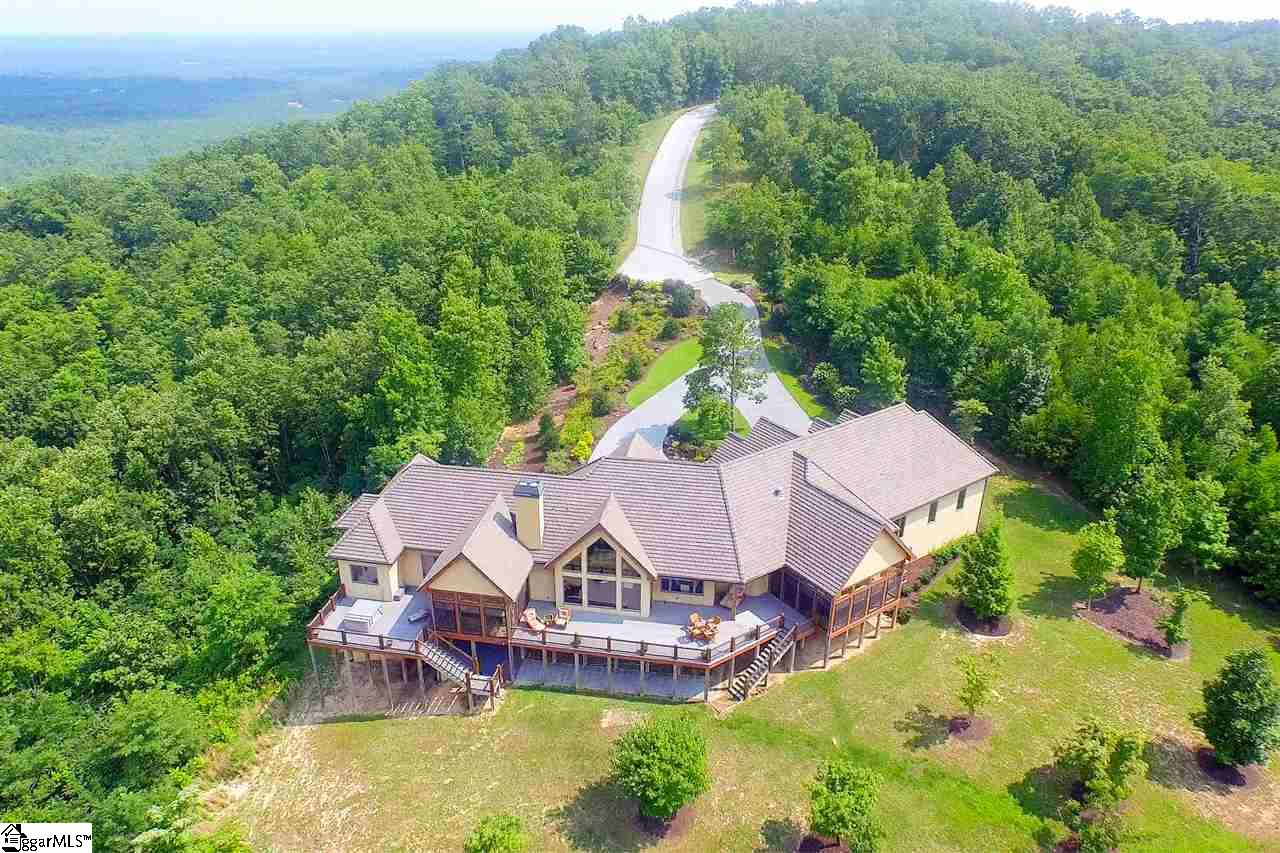 Come home to The Cliffs at Glassy, The Cliffs' original gated golf and wellness community atop Glassy Mountain in Landrum, SC. This tranquil five acre mountain estate offers 360 degree views and borders 12,000 acres of protected wilderness area. The home, constructed with stone, stucco and a cement shingle roof, blends with the colors of nature and is as one with the mountain. Facing the beauty of Hog Back Mountain is 2000 square feet of decking. A closed porch with a fireplace, screens and sliding panels provides 600 square feet of extra year-round living space. Yard has room to add a swimming pool. You may also relax on the private sun deck and enjoy the hot tub. Enter the home and you will see exquisite craftsmanship, masterful design and superior construction. Whether cooking in the gourmet kitchen or relaxing in the vaulted great room, the open plan is perfect for entertaining small groups or a crowd. The magnificent master suite is an extravagance all its own with large dressing area, relaxing bathing area and private outdoor living space with beautiful flagstone floors. The lower level can be used as a studio or mother-in-law suite and has its own exercise area and steam shower, along with a private entrance. Newly renovated in winter 2019 with an added staircase in the great room to access the lower level. A Cliffs club membership is available for purchase with the home.
