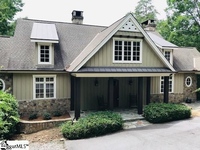 1.02 private acres on fabulous Lake Keowee, with covered boathouse & lift over deep water. Turn-key condition, fully furnished and ready to enjoy! 4 or 5 bedrooms (bonus room over det. garage with full bath makes an excellent teenager-suite) and 4.5 bathrooms. Many special features incl. low-maintenance exterior with stone and board & batten siding; mature landscaping; wormy oak entry door; wainscoted staircase to finished space above 2-car courtyard-entry gar.; slate and hardwood/hickory floors;  lodge-style great room with 3-tiered deer-head chandelier centerpiece, gas-log fireplace with slate hearth and gorgeous cathedral/wood-lined ceiling; cozy and curtained library nook with built-in bookcases; kitchen lined with hand-rubbed cabinetry, a spacious wood-topped island, honed-granite countertops and GE Profile appliances; numerous French doors lead to an expansive covered porch and stone-arched flagstone terrace; screened porch with stone, wood-burning fireplace just off main living space; 2 master-suites, each with double-door access to en suite bathrooms; marble-topped dresser vanity and wrought iron fixtures in half bath; lower level media/rec room with a convenient kitchenette; custom window-treatments and professionally designed interior decor; all with excellent Lake Keowee waterfront space and inviting views from the flagstone lakeside patio. Lake living at it's finest!