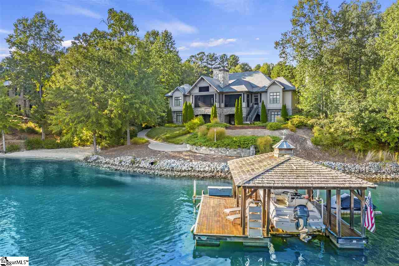These original owners of this incredible lake front estate are also among the original founders of the Reserve at Lake Keowee. This world-reknowned resort community with golf, tennis, marina, pools, and more is 50 minutes from Greenville's magnetic Downtown and world class health care, only 30 minutes to Clemson. This choice lot on deep water with sweeping views is the perfect setting for this home DESIGNED FOR TWO FAMILIES TO SHARE! Four master suites, all with lake views! Two masters on main, two more on Terrace Level. Flex Room with fifth bath used as fifth bedroom. Spectacular covered porches on both levels feature stone fireplaces, and main level porch includes vaulted ceiling and retractable screens -- the best seat in the house to watch The Game. Architecturally designed, built with enduring quality, from the slate roof to extensive gardens and hardscape, with easy cart path to the shore and dock.  Showings ltd to serious qualified buyers. 24 hour notice. Listing Agent must be present.