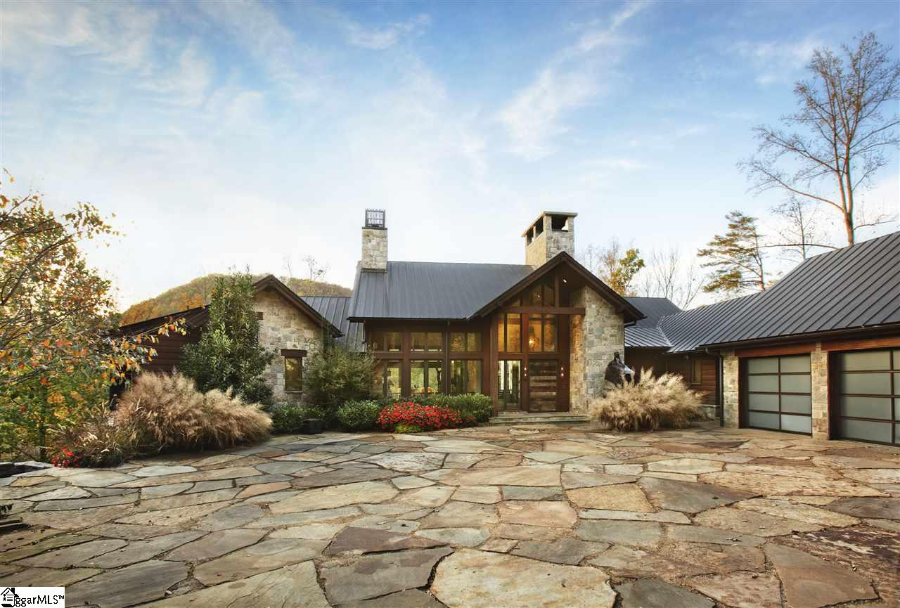 World-class architecture and authentic South African culture is infused into every detail of this two-story luxury masterpiece. An idyllic setting at the end of a private cul-de-sac overlooks the Saluda River and the seventh green of The Cliffs at Mountain Park, a Gary Player Signature Design course. The natural aspects of this mountain estate are complete with walking trails, various statues, and an infinity edge pool to fully embrace outdoor mountain living. The stone and hardwood exterior, copper roof, huge inviting windows and four-car garage with glass doors, create a stunning exterior and welcoming entry as one approaches the house by the custom driveway with massive river stones brought in from Colorado.   As one enters the home, prepare to be wowed by stunning design and a warm, welcoming feel. The main level boasts fantastic indoor/outdoor spaces with a sizable terrace with retractable screens and 1 of 5 gas fireplaces. Designed for cooking extravagant meals, the gourmet kitchen offers high end appliances and ample counter space with two large granite islands. There are plenty of areas to dine off the kitchen with a breakfast room, dining room, or walk out to the screened in terrace with a built-in grill that makes a perfect third dining space on cooler fall evenings.   A luxurious master suite resides on the main level with incredible mountain views off the adjacent deck. The stairs lead down to expanded living spaces that feature two recreation rooms divided by a double sided fireplace and also feature a kitchenette, a second master bedroom, and three more guest bedroom suites for hosting family and friends. Outdoor spaces continue to be an essential focus on the lower level. Walk out to the oversized patio or take a swim in the awe-inspiring infinity edge pool with underwater speakers.   Strict attention to detail has been emphasized in every facet of this extravagant home which has been meticulously maintained. One will truly get a slice of South Africa within the Blue Ridge Mountains in this special real estate offering. A Cliffs Club membership is available with this property.