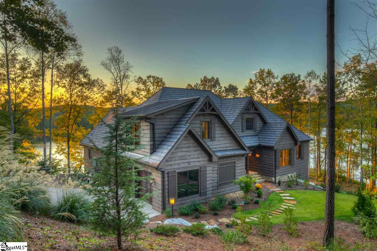 At just a year old, this still-new home offers over 300 feet of shoreline,180-degree views across Lake Keowee—including spectacular sunsets and glimpses of The Reserve's golf course—and a flexible, social floor plan that allows for up to seven bedrooms when needed. A breezy jaunt of around 30 steps separates the house from its custom covered dock, resulting in an enviable everyday-meets-vacation lifestyle.   The exterior blends thick wavy-edge pine siding, shake roof, and Doggett Mountain stone accents. Extensive boulder retaining walls line portions of the drive and motor court. Lakefront outdoor living areas occupy the home's rear and side: A broad main-level covered deck wraps to a screened porch with stone fireplace, the ideal spot for toasting sunsets year-round. A stone terrace follows the same footprint on the lower level.   The interior opens to a great room that combines foyer, living, dining, and kitchen areas while eliminating walls that might block the view. A hefty stone fireplace, tongue-and-groove ceiling, and hand-scraped flooring lend a rustic mood to the light-filled space. Pella doors and windows outline the views with quality.   Outfitted with Thermador and Bosch appliances, farmhouse sink, and hall pantry, the kitchen is defined by an angled granite island with counter-height seating. The island's wood-toned base matches that found on the beautifully crafted range hood and contrasts with light custom cabinetry elsewhere in the kitchen.   The left wing has the master suite, where dusky blue walls mimic the water and play against the white plank ceiling. In the en suite, a double shower and free-standing soaking tub are spa-worthy. The main level's opposite wing houses two bedrooms and two full baths. An office off the foyer can pull double duty as this level's fourth bedroom.   Stairs near the oversized garage lead to an expansive bonus room/guest suite with full bath. The lower level includes a party-sized family room with board-and-batten wains