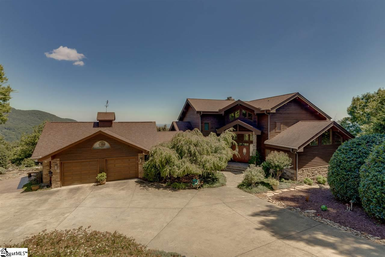 """Come experience the ultimate mountain family retreat in one of the most private settings at the Cliffs at Glassy. You will be immediately captivated by the charm of this cedar home with many large windows to take in the sights. Experience """"wow"""" views to the NE and south of Hogback Mountain where the distant valley can also be seen from nearly every room in the home. The mountain views of nearly 180 degrees are also protected with surrounding conservation area below. Comfortably host your extended family or guests with 5 bedrooms and 5 ½ baths on 3 levels or invite your golf friends to stay and experience the unprecedented amenities and golf experience of the Cliffs seven private courses. Take your pick of many living spaces, both inside and outside the home including a great room with a double-sided fireplace, kitchen with a large granite island, dining room that resembles a sunroom with a glass wall and ceiling, and two large decks. The master bedroom is spacious and features a plush master bathroom with """"his and hers"""" closets. An upper level with a balcony that overlooks the great room provides a study with a gas fireplace and two guest bedrooms. Walk down to the gracious lower level to workout room, recreation room with a gas fireplace and walkout deck, a wine cellar, and two additional guest bedrooms. The grassy backyard is level and great for dog lovers with plenty of space for them to run and play. The side yard also has a soothing water feature and coy pond. This is the perfect home for a primary residence or a mountain getaway! Furniture, appliances, and TV's are included in the purchase. A Cliffs Club membership is available with the property."""