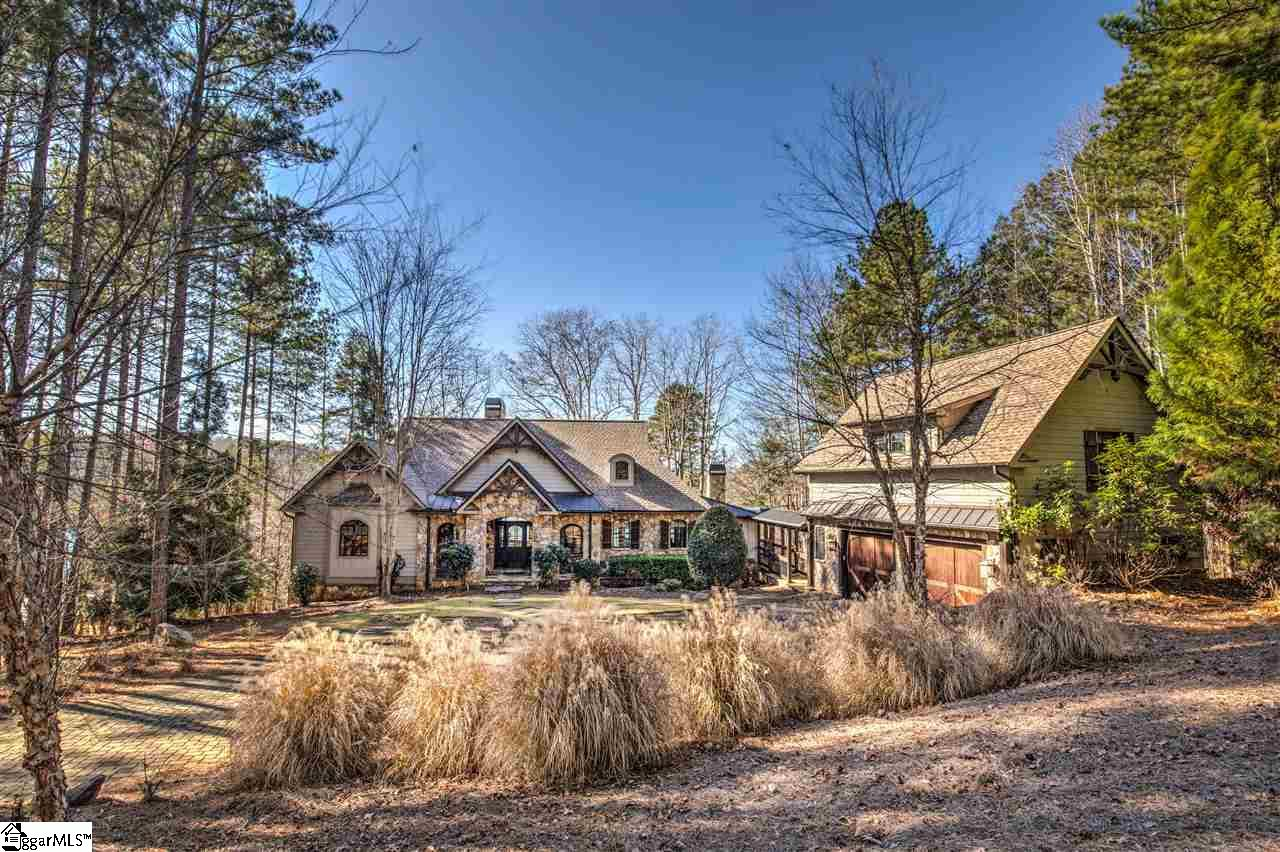 Situated at the end of a cul-de-sac on 1.11 private acres in The Cliffs at Keowee Springs, with 160 feet of waterfront, this Evergreen Construction custom home is the epitome of lake living.  At 4,995 sq ft, with 4 bedrooms plus bunk room, 4-1/2 baths, main floor master and two expansive lower level guest suites and a separate guest suite with kitchenette over the garage, this Craftsman style lake home is comfortable, open, inviting and designed for family fun.  The lake views are long and the walk to the covered slip dock is short and easy from the gently sloping home site.  Outdoor living areas include lakeside open and screened porches, a grilling deck convenient to the kitchen, a lower level terrace with double door access, a lake room for water toy storage, and two fireplaces which complement the two additional interior fireplaces.  The great room is vaulted and the ceiling lined with T&G pine, the floors are heart pine, and there's a contrasting floor to ceiling stone fireplace and other additional millwork features in the home.  Granite counters, WOLF and SUB ZERO appliances, washer and dryer, as well as designer furnishings (included) make this home convenient, cozy and move in ready!   Additional features include a lakeside waterfall and firepit to provide additional exterior enjoyment.  The lower level recreation room is comfortably furnished for tv time, yet large enough to accommodate a ping pong (included) or pool table.   The double car garage opens to a large paver stone motor court with plenty of room for multiple vehicles or a basketball game!  Located in The Cliffs at Keowee Springs, this charming residence is just a short drive or stroll to the fitness and golf activity center.  The Springs clubhouse plans are finalized and construction begins in 2020, which is sure to elevate property values.  The new Springs clubhouse will be the first planned and executed by South Street Partners, and is sure to be The Cliffs best, based on the design plans mad