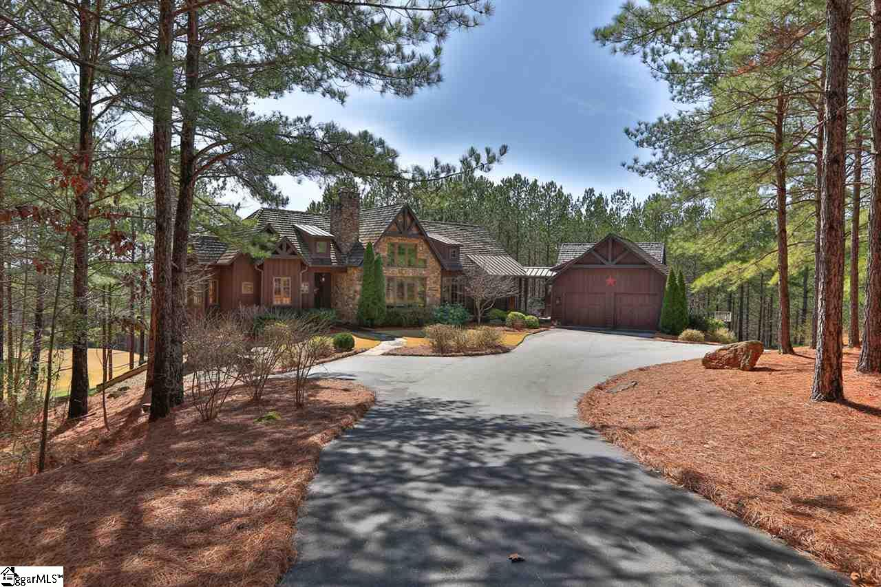 "The features of this beautiful home check more boxes than you might have on your list! The main house plus separate guest quarters will appeal to buyers with large families and/or friends they love to have visit. Anyone looking to invest in a home with others? No better floorplan. Hoping for rental income to defray costs? Guest ""house"" checks that box. Car aficionados will appreciate the five-car + capacity that the two oversized garages offer.  Situated on almost 3 acres with superior set back from both the road and golf course, the true sense of privacy belies the fact you are actually in a well populated gated community. The rear of the home enjoys an elevated view of the #6 green of the Reserve's Jack Nicklaus Signature Golf Course but from a distance that is perfect to take in the spectacular view without any of the noise. The main house boasts vaulted ceilings, stone fireplaces, awesome views and great outdoor living space. The open floor plan flows smoothly from the Great Room through the dining room and in to the eat-in kitchen. Upon entering the home, you will immediately appreciate the views. The Great Room and Screened Porch are across from each other, functioning as one large entertainment space when desired. Both boast vaulted wood ceilings and a stacked stone fireplace. The open Dining Room allows the ambience of the fireplace to be enjoyed during a leisurely meal. A spacious eat-in kitchen adjoins the Dining Room and features a breakfast nook at one end where lingering over coffee while taking in the views is a wonderful way to start your day. The hallway from the breezeway to the kitchen is where you will find a half bath and laundry. The master is secluded at one end of the home featuring a vaulted wood-lined ceiling and beautiful golf course views. Bathroom highlights include double vanities, large walk-in closet with built-ins, a tiled walk-in shower and jetted soaking tub. Descending the wide, light-filled staircase to the terrace level you are greeted by a convenient refreshment bar that services a recreation room and covered patio activity. A stone fireplace is the focal point of the spacious Rec Room which opens directly to the patio.  Completing this inviting space for family and friends are three large bedrooms and two full baths.  Connected to the home by a common breezeway, the two-bay garage services the main house while the three-bay garage is the foundation for the amazing ""guest house"". The guest quarters operate more like a guest house with vaulted ceiling Great Room spilling out to a private deck, full kitchen with granite top island, two ensuite bedrooms one being a four-bed bunkroom, powder room and a loft overlooking the Great Room. Below the guest quarters, the oversized three-bay garage is enjoyed by current owners as an indoor/outdoor game room. The drive in from the front yard creates a courtyard at the entrance of this structure allowing for plenty of parking or ""shooting hoops"".  Facing the view, you have doors and windows as well as a covered patio. Owners utilize a portion of the garage space for FUN, having equipped it with shuffleboard, air hockey, foosball, pool table, diner-style table & chairs and of course several mandatory TV's!! That still leaves room for one car AND a golf cart. The space is heated and cooled, has an epoxy floor finish and enjoys a convenient half bath. Open the front and rear doors on game day and invite the neighbors to PARTY from courtyard to course! Be sure and watch the video tour that captures the essence of this home's amazing setting!  Premier Membership is available."