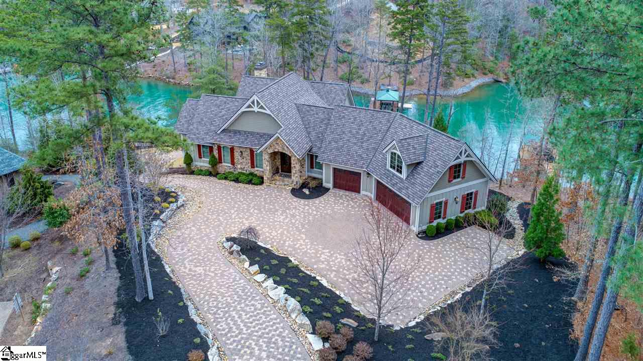 Offering the tranquil waters of a deep cove, yet perfectly positioned to capture incredibly long views of Lake Keowee's main channel and distant mountains, 115 Mossy Way is a generous home designed for sharing with family and friends.   A large paver motor court with center medallion (and plenty of guest parking) sets the stage for the impressive stone arched entry. Inside, past the vaulted foyer, the great room showcases the view through walls of windows. Open spaces that flow to the dining area and kitchen feature rustic white oak flooring, stone fireplace, and corner bar with wine cooler. To the left, glass doors recede for seamless entry to the wide lakeside screened porch with fireplace and built-in grill. To the right, the kitchen is well equipped with custom glazed cabinetry, double Thermador Professional convection ovens, steam oven, center island with gas cooktop and counter seating, double dishwashers, wine cooler, professional-sized fridge (a second fridge is in the laundry room), walk-in pantry, and double sinks, one of which sits in front of a row of lake-view windows.  The main-level master suite incorporates a trey ceiling, window-lined sitting area, gently weathered shiplap accent wall, porch access, walk-in closet with custom storage, and cedar closet. Vanities wrap one corner of the en-suite bath, while a multi-head shower and soaking tub, backed by an arched window, occupy others.    An extra-wide staircase leads to the lower level, which can also be reached via the elevator. Painted moldings complement the serene tones of the family room and adjacent full galley kitchen with dining area. A lower-level patio frames the lake through stone arches. Three spacious bedroom suites, each with individual ambience and two with captivating lake vistas, accommodate guests, as does a second laundry area tucked behind the kitchen.   Above the oversized three-car garage, a luxurious apartment indulges guests with a sitting room, full kitchen, ample bedroom, and
