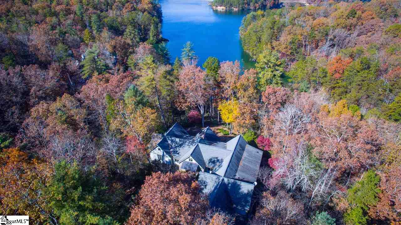 This most unique offering is a gated estate of over 10 acres, set on a perfectly private point with 1,100' of deep water Lake Keowee shoreline. A mile of custom-designed trails meander through mature mixed woodland, underpinned by flowering rhododendron and mountain laurel. The single-level 3,800 SF residence is brimming with custom designed and crafted attributes, including true gourmet kitchen, magnificent twin flue stone fireplace, stone grotto outdoor shower, expansive, 1,200 SF screened porch and two home offices. The meticulously maintained, low-maintenance residence comprises 4 bedrooms with 4.5 bathrooms, including two guest suites and a bunkroom built by an HGTV carpenter. Flooring is of antique Strongbow oak, with countertops of granite and marble. Cabinetry includes a unique pass-through pantry with wormy oak doors to echo the media cabinet and custom-crafted hutch at the end of the 10' long wet bar. Carefully selected details include Charleston gas lanterns, a splendid, 2,000 pound natural stone mantelpiece, extensive lighting and fans, an oversized, pebble-floored shower, and numerous further practical and aesthetic elements. This estate has received preliminary ARB approval for the addition of a second cottage/residence. Family compound possibilities exist for this estate.  A sanctuary of peace in a natural setting, this home gracefully balances casual indoor and outdoor lake living in its own oasis within the Cliffs at Keowee Vineyards community.