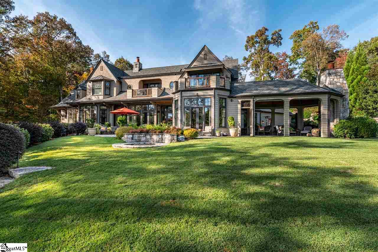 Generously endowed with natural, architectural and aesthetic charm, this listing represents one of the finest properties on Lake Keowee.  From its enviable situation on a premier, south-facing waterfront lot with golf course and State Park views to its timeless character and luxurious finishes, no detail has been overlooked.  Precisely poised to capitalize on privacy, slope and exposure, the boutique architecture is at once enchanting, comfortable and practical. Inviting living spaces extend over three levels (with the option of an elevator), and overflow onto balconies and patios,  and on … to the lawn, beach and tree-hung lot. Spacious interior and exterior dining and entertaining areas radiate from a chef's kitchen of magnificent proportions, replete with high-end appliances set in eye-catching granite and wood worktops. Beyond generous kitchen pocket doors, the heated, flagstone-floored patio has screens that drop down at the touch of a button, or raise for access to gardens and a lawn sufficient for croquet or badminton. The bright living room, with its inviting window seat and marble flush-to-floor hearth is underpinned with solid quarter-sawn white oak flooring, as is the dining room to which it lies adjacent beyond one of many graceful arched openings.  While all five en suite bedrooms (one presently serving as a second home office) are generously sized, the prime bedroom possesses sublime proportions, a reading alcove with restful lake views, sumptuous onyx bathroom, and well-appointed walk-in closets. Upstairs, a media room with private balcony and snacking kitchen stands ready to produce either popcorn or coffee. At lake level, an exercise room and bunk room share one of six full (plus two half) bathrooms, an outdoor shower and beach access. Bespoke cabinetry throughout is by Morgan Creek Cabinets. Bountiful storage options include two substantial heated rooms that could easily convert to further living space. Exceptional millwork, exquisite plumbing and 