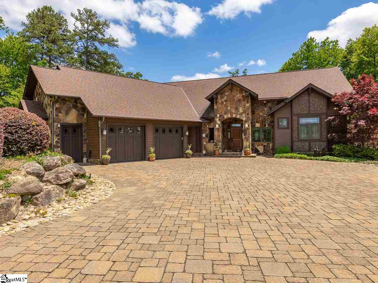 """This Mountain Retreat is glamour, style, and true Mission architecture features in one perfectly composed home!  No detail was overlooked when this home was built.  The layout allows for entertaining, with large groups, as well as smaller groups of people, being in the home at one time for a gathering!  This is possible due to the flow from the Great Lodge Room to the Dining and Kitchen to a screened in porch or decks.  Continual flow in and outdoors for optimum entertaining.  Your guests will love that feature because they get to experience nature, mountain views and the sound of a babbling brook with the waterfall feature in the landscape below the deck.  Spectacular luxury finishes showcased like rough hewn beams wrapped in wrought iron strappings , custom chandeliers of wood and rod iron, stained glass transoms above doors, Solid core oak doors,and hardwoods throughout. Custom quarter sewn oak, Mission style cabinets, throughout the home.  The kitchen has Wolf, Subzero and Miele appliances including double ovens, trash compactor, ice maker, and wine rack.  The Master suite is on the main level along with his and her office spaces. Two other bedrooms with full baths are on the lower level along with living room with fireplace.  All walk out to a covered patio, hammock, water feature and nature itself. Be sure to take the virtual tour so you can walk through the home as if you were there.  Everyday you can come home to your very own mountain retreat!  Each day you are greeted with breath taking sunrises and mountain views.  This home has a two car garage and a third golf cart garage. This home also sits on top of the 2.16 acres giving it the privacy and seclusion while being minutes from the front gate of this amazing gated community.  Video is also available for this property.  Every detail will capture your attention in this home and the layout will impress you for flow, function and livability. The """"prize"""" with the home is the unbelievable amenities, including """