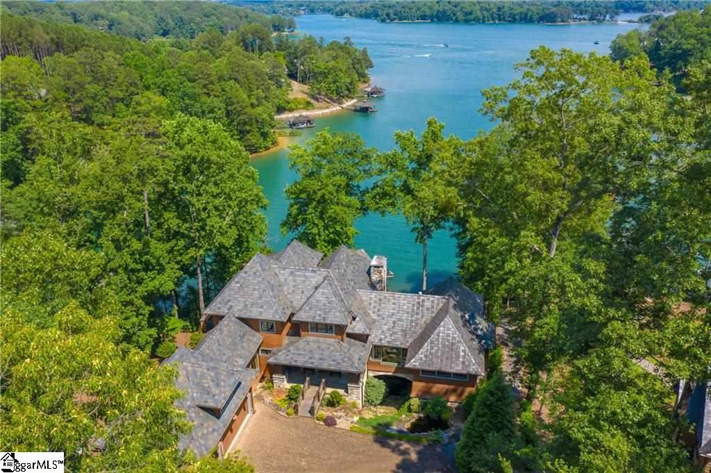 MAGNIFICENT is the word that comes to mind for this private home, from the views to entertaining spaces to outdoor living. One of The Reserve's finest homes exudes elegance and luxury!!! Enjoy wide open views of Lake Keowee from this premier homesite, starting as you enter the driveway and continuing all the way to the lakeshore. Just imagine: enjoy your morning coffee at sunrise on a spring morning from the screened porch; float and laugh with your family off the dock on a summer afternoon; bask in the light of a harvest moon on a fall evening by the fire pit. And at all times you'll be taking in the open lake views, and relaxing to the peaceful sounds of the waterfall. Entertain family and friends on three levels, all offering varied experiences. The main floor, full of natural light from the large view windows, is the heart of the home. In the well-appointed cook's kitchen, guests will sit at the island, enjoying one another's company. Brunch or dinner in the dining area will have everyone mesmerized by the lake. If a relaxing evening is on the menu, retire to the living room to enjoy a movie, or to the study to sit by the fire and curl up with a book. The master suite also offers incredible views, a private porch, comfortable spaces, and utmost privacy. The lower level offers a media space by the fireplace, a theater, and a luxurious bar area. If privacy is important to your guests, there is a cozy, en suite guest house connected to the lower level as well. And on the upper floor, you'll find a common sitting area adjacent to two guest bedrooms, also en suite. This lovely home provides plenty of comfortable spaces, while maximizing expansive views of Lake Keowee. It's the perfect respite, offering relaxation and serenity. And it is only a short drive to the vibrant amenities of The Reserve - including golf, marina, fitness center, clubhouse, pools, walking trails….and so much more!!! Appointment required. 24 hours notice to show.