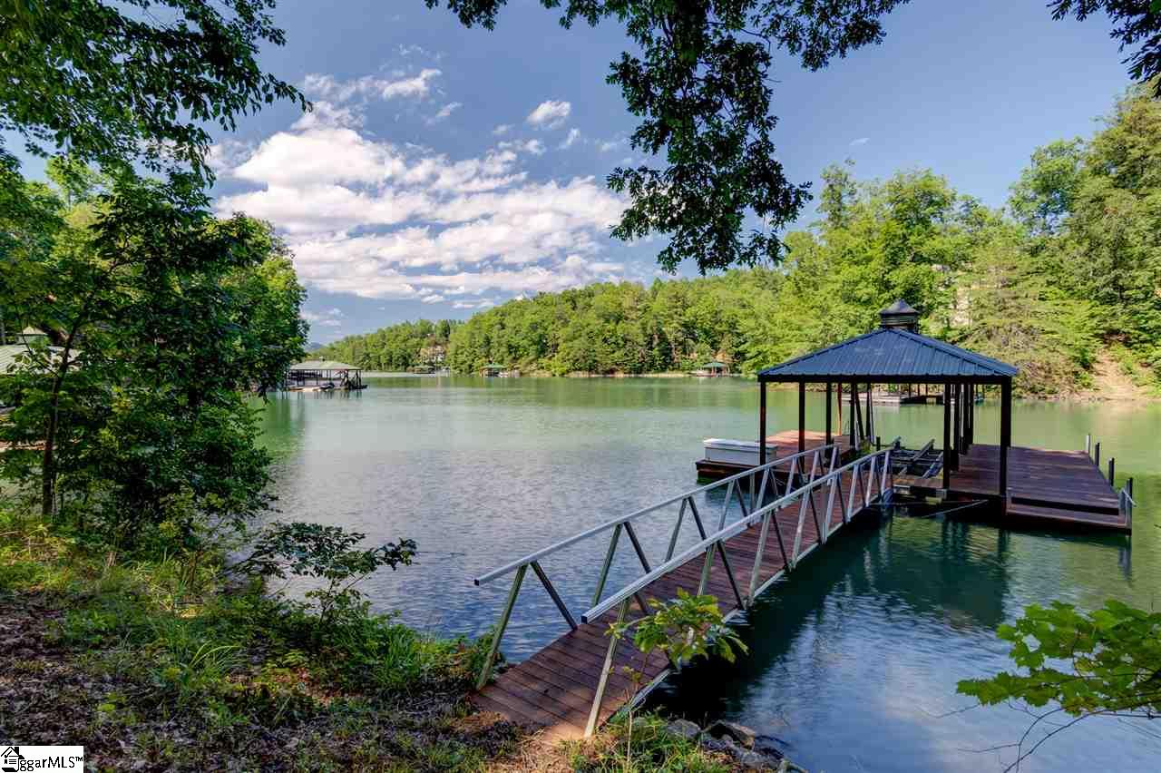This waterfront homesite features beautiful layered mountain views, mature hardwoods and a slope to  build a walkout the shore and covered dock with boat lift.   The property is situated in a cul-de-sac along a quiet cove. The Cliffs at Keowee Springs is a private gated community just a short drive to area townships like Clemson, home of Clemson University and Seneca for shopping, conveniences and entertainment. Amenities are accessed by membership. A Multi-level membership is available with separate purchase to enjoy the amenities at all seven Cliffs communities. Experience amenities of championship golf, tennis, walking trails, pools, clubhouses, and walk or ride to the Beach Club (only at Keowee Springs) with its pools, slides and of course the sandy beach for paddle boarding or kayaking. The Cliffs takes pride in the many programming opportunities that go along with ownership. You are not just purchasing a homesite, it is a lifestyle with something for all ages.