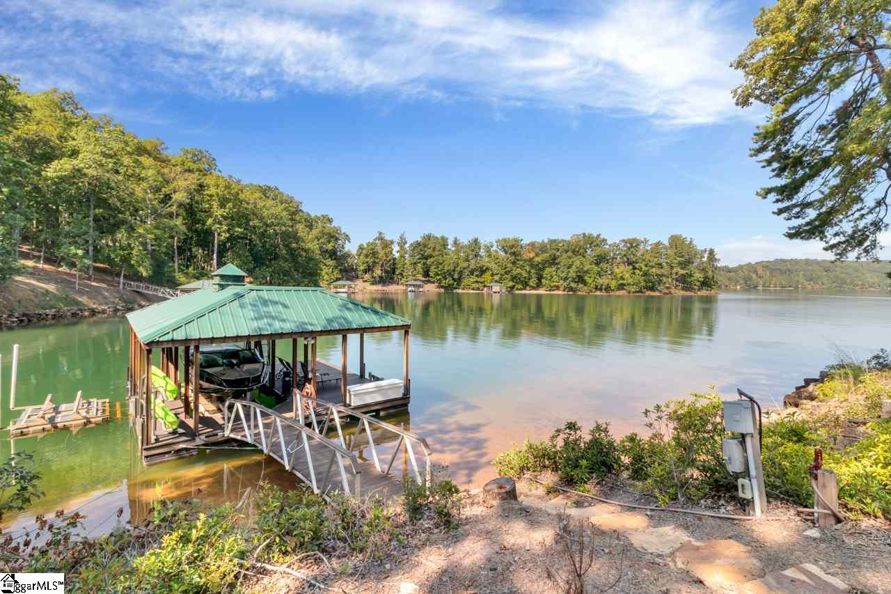 Beautiful waterfront home in a prestigious section of the Cliffs at Keowee Springs! This 5 bedroom plus office Craftsman style home has approximately 5161 square feet of indoor living space that includes an in-law suite above the garage with a full bathroom. Enjoy a three season sun porch with retractable/sliding windows and screens, a wood burning fireplace, lower level covered outdoor living space, and a grilling deck conveniently nestled close to the kitchen. This home features custom cabinetry, concrete and granite countertops, an office on the main level, large mud room, full kitchenette in lower level and plenty of outdoor space both covered and uncovered for you to enjoy all that Lake Keowee has to offer. Lots of details truly make this a smart home with a complete Smart Home Control4 system, wiring for a full house security system, and even a generator for the entire home! Ideal for family and entertaining guests. This home is located in the Cliffs at Keowee Springs gated community, close to Clemson University and area conveniences. Enjoy this private club experience with seven clubs, fine and casual dining experiences, seven championship golf courses (including three on Lake Keowee), Beach Club, walking trails, and wellness facilities.