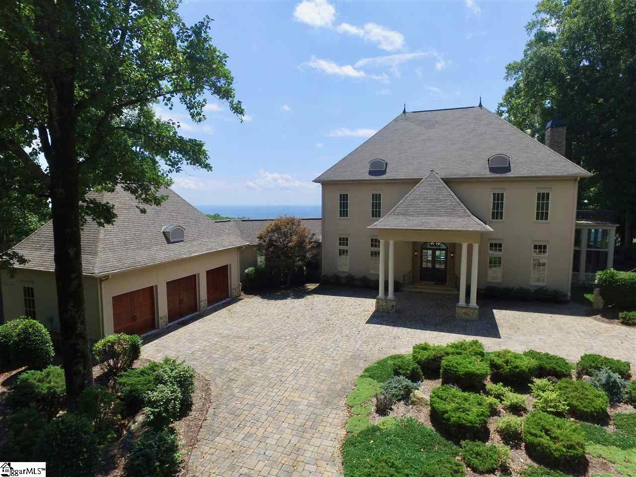 Come home to The Cliffs at Glassy, The Cliffs' original gated golf and wellness community atop Glassy Mountain in Landrum, SC.   From the minute you walk through the front door of this mountaintop estate situated on 3.29 acres, you know you are at the top of the world. Expansive floor-to-ceiling windows overlook a 70-mile vista of verdant valleys, the Blue Ridge escarpment, and – at night – the twinkly lights of the towns below.  On July 4 you look down at the fireworks!    You are immediately enveloped in serenity as you walk through this unique, custom-designed home. Three floors of large, open spaces are cozy enough for quality time together or to spread out in your own quarters and soak up the incredible mountain setting.  Unexpected touches delight: An elevator with walls padded in toile fabric.  A butler's pantry with a pull-out linen rack. Kitchen outlets tucked beneath cabinets so that granite spans from countertops to cabinet bottoms. High ceilings on every floor.  Quarter-sawn oak hardwood flooring and cherry cabinetry.  Showers with windows (this house showcases its incredible views at every opportunity.)  Four generous bedrooms and two equally large office/dens.  A fireplace in the master bedroom – and a private deck.  Four bathrooms and two powder rooms with unique tile and decorative treatments.  The open kitchen includes two dishwashers and two ovens.  The upper level boasts a laundry chute to make life easy.  Throughout, there are large closets, beautiful built-ins and well-designed cabinets to provide outstanding storage space.  And, of course, there's a full-house sound system, central vac, and wireless internet.  The main floor has a screened porch and a deck; the lower floor has a deck and a yard with wrought-iron fencing.  At nearly 3,000 feet in elevation with a sophisticated sensibility, this is a home equally comfortable for a quiet family evening or large scale entertaining.  Conveniently located half way between Asheville NC and Greenville 
