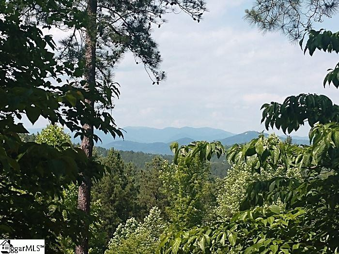 Beautiful mountain views from the level building site at the top of this lot! Enjoy cocktails and dinner from your new covered deck or patio on this 1.84 acre lot overlooking the Blue Ridge Mtns! Very peaceful setting to listen to the sounds of nature and feel that gentle breeze. This home site has a level building site that drops off to expose the mountain view to the north. The Beach Club is just minutes away offering great entertainment for family and guests featuring two pools, slides, kayaks, paddle boards, full bar and food service plus boat slips for lease and day use. Stroll down the walking trails and enjoy casual dining at the remodeled and expanded Bistro Restaurant. The gated community of the Cliffs at Keowee Springs is home to a Tom Fazio championship golf course with a unique design with three loops of six holes and the Bistro as a centerpiece. Amenities noted are specific to community in which home site is located. Club amenities are accessed by club membership only. Different levels are available for purchase with property. Membership is available with separate purchase where you can choose the level that best fits your Cliffs living. Membership must be declared at time of offer and paid for at closing. Only a short drive in to Clemson and 45 minutes to downtown Greenville.