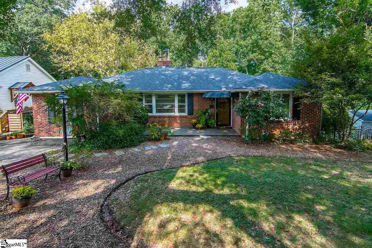 Fantastic location just a few minutes from downtown Greenville, I-385, and Bob Jones University. The 26-acre Timmons Park and its premier disc-golf course, pickle ball courts, baseball field, hiking/biking trails and playground are just down the street!  This well maintained classic mid-century 3/4-bedroom, 2 1/2 bath brick home has it all, including many updates giving you the charm of the old, and the conveniences of the new. Classic elements include picture molding and hardwood floors throughout, built-in cabinets and two working fireplaces, one with gas logs, the other wood burning. A side entrance leads into a room used currently as a music studio, which could also function as a formal dining room or office. The custom kitchen includes oak cabinets, stunning River Gold granite and stainless appliances, including a dual-fuel cooktop and convection oven. Downstairs is a small workshop, a large utility/laundry room with extensive counter space for crafts or hobbies, a spacious den with fireplace, and a separate living suite. The basement suite with bedroom, bathroom and full kitchen could function as an in-law residence or rental. This walkout level opens to a gated and fenced patio overlooking the back yard.  The back yard features a 10 x 12' storage/workshop building with electricity and ramp access. The top portion of the back yard is fenced for pets, and the lower is your personal wooded nature sanctuary, including a creek. Roof, HVAC (both AC and furnace) and rear fence are new in 2019.  The electrical system was upgraded to code by owner, a certified electrician, who also added motion security lighting. Stained glass and appliances convey with the house. (The wood stove does not). Don't miss this opportunity to own a distinctive home between the historic Overbrook and North Main neighborhoods, in the shadow of the Gassaway Mansion.  Call today for additional information or your private showing.