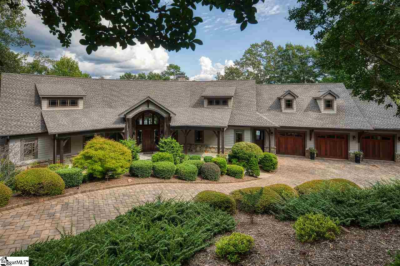 This gorgeous lake front home is perched on two lush acres in Cliffs Keowee Falls South with 400+ feet of shoreline and 180-degree views of Lake Keowee from almost every room! It features a dramatic, bright and open floor plan with wood beam accents and large floor to ceiling windows and doors overlooking the lake. The style is timeless, a perfect mix of Craftsman with Modern Classic. All this adds up to a grand 4 bedroom, 4 ½ bathroom 6,000 sq. ft. home that is both stylish and comfortable. A perfect lake house! The main level includes American walnut floors and high end finishes and details throughout, and is perfect for entertaining with a very large great room with two seating areas, kitchen with bar and extra large pantry and dining area with great lake views. A double-sided fireplace sits between two dramatic stone archways and can be enjoyed from both the great room and kitchen/dining areas. An added bonus are two separate office/den areas on the main level along with a powder room. Just steps from the kitchen is a lovely outdoor room overlooking the lake - perfect for a morning coffee, reading and entertaining while taking in the beauty of the lake. A huge 50' balcony/deck off the family/dining overlooks the lake and the lush landscaping with a water feature. It features 6 waterfalls flowing down through massive boulders towards the lake. It is a magical focal point--especially with lights in the evening.. The large master suite is elegant and also enjoys long lake views. The master bath is a place you'll want to relax and enjoy with a lavish tub and oversized shower. A true SPA like experience. A spacious laundry room is conveniently located next to the master. The lower level can be reached via the wood-paneled elevator near the kitchen or the uniquely designed stairway. A huge den/game area with 10 ft. ceilings, a large stone fireplace, and kitchenette/bar is perfect for family fun and watching your favorite sporting events. Your guests may never leave on