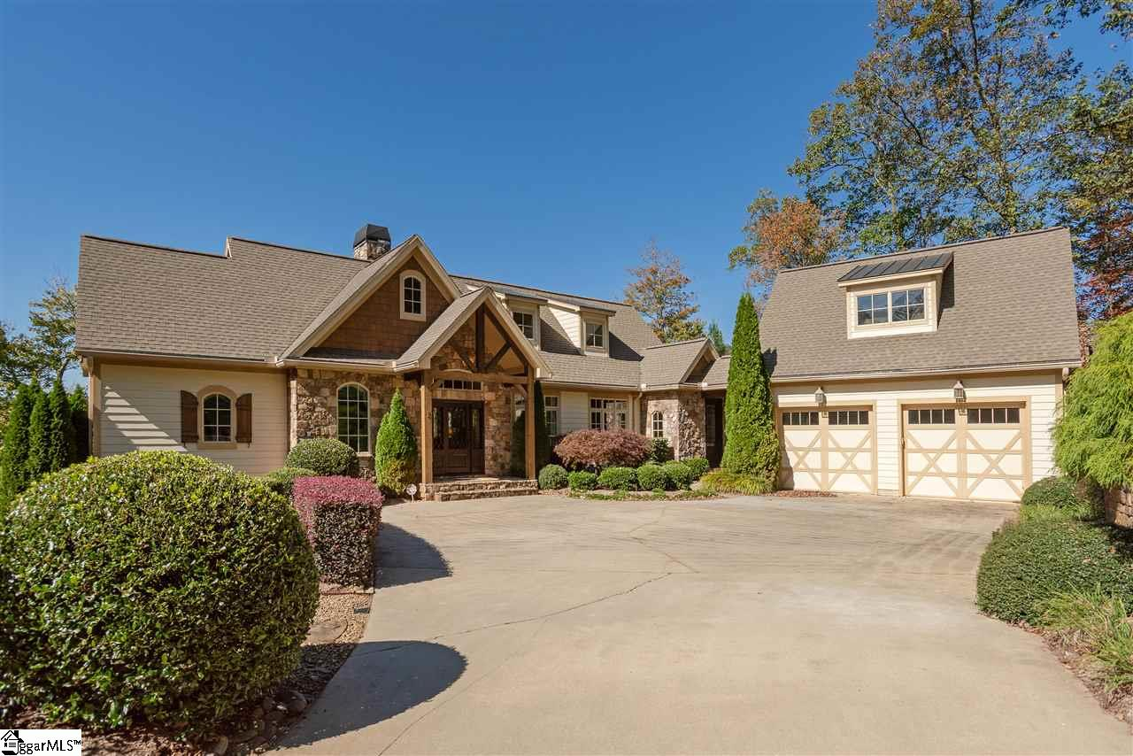 """Nestled in the mountains just minutes from Greenville, SC, make yourself at home in the comfort and convenience of The Cliffs Valley gated golf and wellness community.   Privately located at a high elevation of 2,600+ feet sits a beautiful European style home with panoramic, rolling mountain views from the southwest to the northeast directions. When approaching the home one will appreciate the stunning curb appeal with well maintained landscaping and a level driveway, providing effortless access to the home. The home's exterior includes a mix of hardie board and field stone with 30-year architectural shingles over the main roof and copper roofs over the dormers.   Step into the foyer to witness the rustic interior with a desirable, open floor plan, quality finishes, high cathedral ceilings, and highlighted with large windows that frame the awe-inspiring views. The main level offers impressive living spaces, including a great room with a field stone gas fireplace and a kitchen with granite countertops, Viking appliances, and custom cabinetry. An oversized dining room is also adjacent to the great room and kitchen. Begin the day with a cup of coffee by the fireplace on the welcoming screened porch. The master suite also resides on the main and includes trey ceilings, """"his and hers"""" walk-in closets, a walk-out deck and plush master bath with plenty of natural light, and large soaking tub.   The lower level is impeccably designed and warm and inviting for overnight visitors. Three generous guest bedrooms are connected by a hallway off the spacious recreation room that includes a wet bar, adjoining wine cellar, and another field stone fireplace.  From the recreation room, walk out to a sizable, covered second deck. A large amount of unfinished storage space is also located on the lower level. At just over 3,200 square feet, the home is effortless to maintain!   Incredible convenience the Valley North gate to easily access Highway 25 to Hendersonville, NC or Greenville, S"""