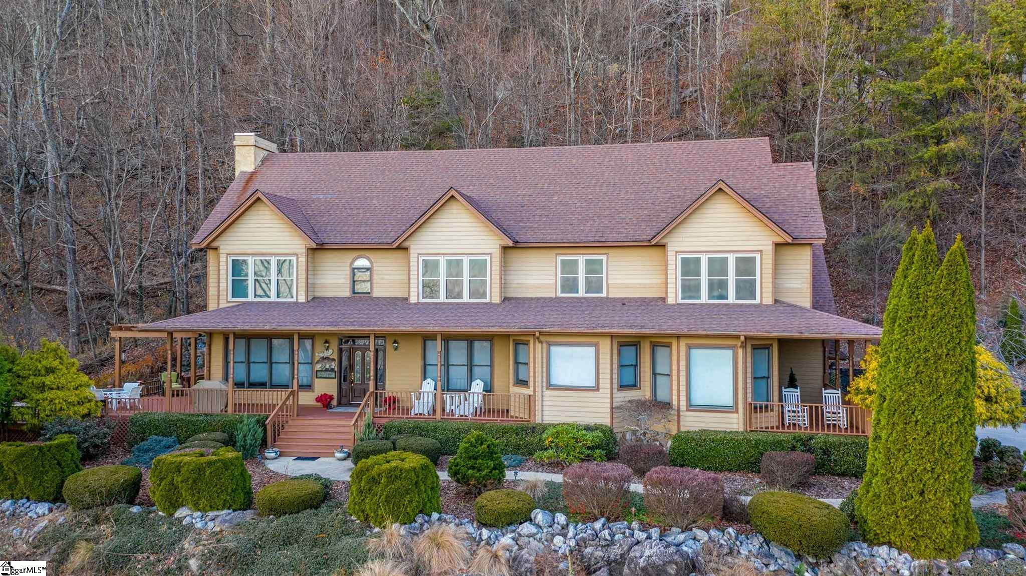This fabulous home is perched at the top of Plumley Summit Drive, overlooking all of Glassy Mountain!  Experience the beauty of this welcoming home.  At 2100ft, you can see the Blue Ridge Escarpment during the day and thousands of twinkling lights at night.  Enjoy the relief of the cool breezes in the Summer, see the mountainside burst into Fall color, watch the pristine snow cover the mountain peaks and see the landscape come to life with the dawn of Spring.  Imagine entertaining your friends and family in your cozy living room in front of a roaring fire on a cool evening or lounging in the hot tub with this awe-inspiring view while listening to the sound of running water from the 50-foot waterfall.    The extensive landscaping and expansive front porch add to the curb appeal of this beautiful home.  Entering the beautiful foyer, you are immediately aware of all the upgrades in this home.  You are drawn to the cozy living room with a stone fireplace and the oversized dining room while enjoying the views from every window.  There is a gourmet kitchen with a walk-in pantry, new cherry cabinets, premium granite, a six-burner gas stove/oven, an electric oven, a warmer drawer, a new refrigerator and a large wine cooler.  The island provides generous workspace with room for bar stools.  Imagine your family gathered around the table in the spacious breakfast area enjoying a casual meal together.  Climb the beautiful staircase to all four bedrooms and a laundry.  The spacious master bedroom suite has a large, spa-like bathtub overlooking the outdoor beauty surrounding you.  You will love the huge closet.    There are three more bedrooms each with their own grand view!  There is a large bathroom with two separate wet areas.  You also have a large storage area next to the bathroom that would allow allocating some of that space to another bathroom.   Space available to easily install elevator.  Glassy Mountain is located between Asheville, NC, and Greenville and Spartanburg S