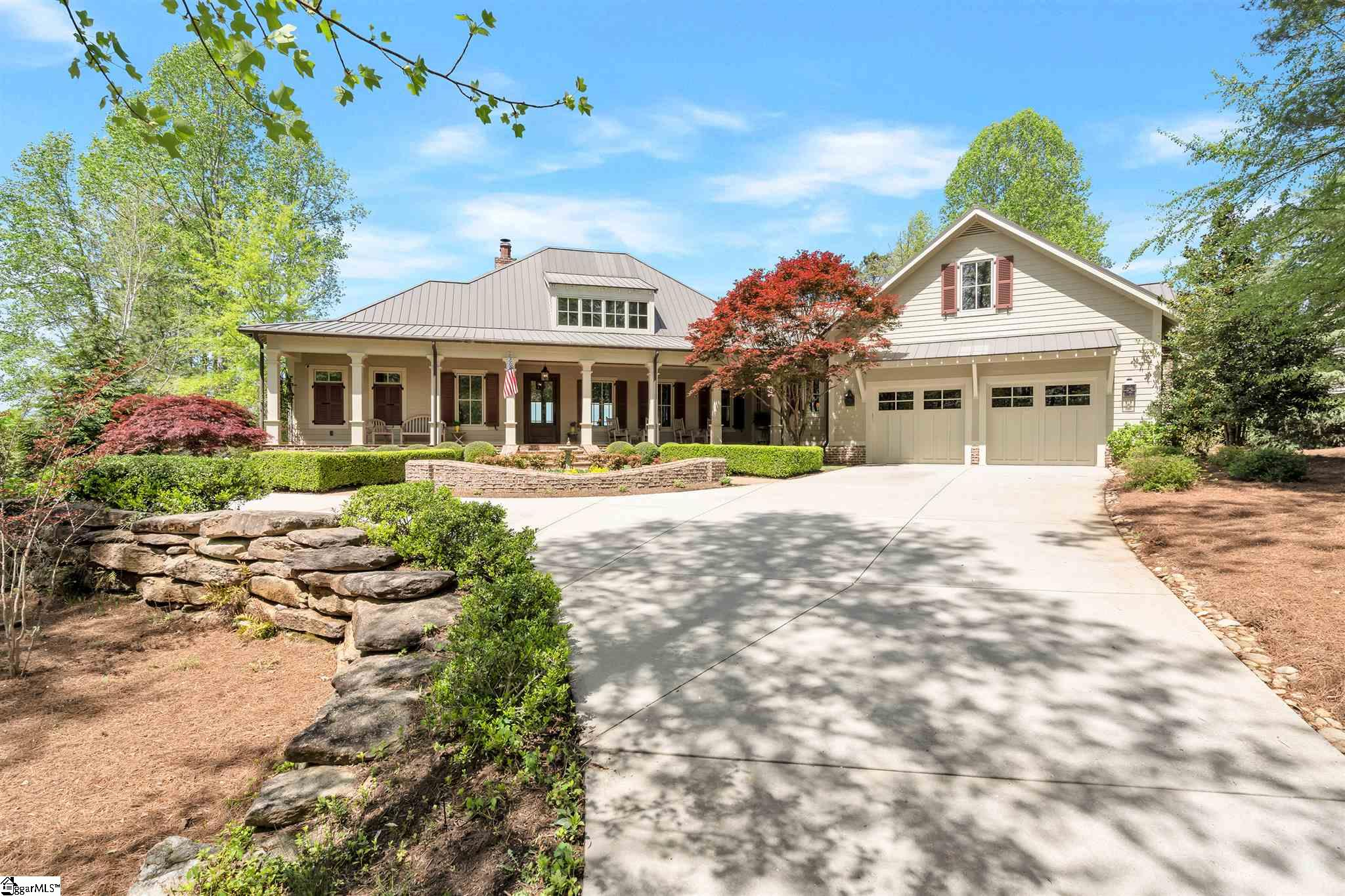 """Relax where elegance meets southern charm with spectacular views of the Blue Ridge Mountains and Lake Keowee! Built by the renowned Goodwin Foust Custom Homes, this 5,100 sq ft home features 4 bedrooms, 3.5 baths and inviting porches to enjoy views and time with friends and family.  The architecture delightfully balances low-country elements amidst unique mountain views, and it is surrounded by a private yard boasting lovely, manicured spaces.  Enjoy sitting on the front porch or one of the two spacious covered outdoor living spaces with friends and family while taking in the private quietness and views this estate offers. Sophisticated luxury continues as you enter the home, where you are greeted by an open floor plan and great natural light.  The home features 3 solid masonry fireplaces with iron screens crafted by local artisans, custom light fixtures throughout, 12"""" rear exterior wall for structural integrity, and 8' solid doors.  You will find honed granite countertops and custom cabinetry in the true chef's kitchen. Prepare meals and entertain in a space filled with top-of-the-line amenities such as the Dacor six burner gas range with dual ovens, a Sub-Zero Refrigerator, convenient appliance drawers, two dishwashers, and an oversized island with a prep sink and dining area.  Start and end your day on the incredible FOUR SEASON porch that will be a family favorite with its blend of natural woods, bead board celling, brick fireplace, and expansive windows to enjoy the views. The BBQ patio with built-in 36-inch gas grill is located right outside the four season porch. Entertaining family and guests has never been easier! On the main level you will also find the owners' suite featuring a tray ceiling and luxurious bath with heated floors. The owners' suite also enjoys custom, spacious closets and a conveniently located laundry room right next door.  On the lower level, featuring shiplap walls, 10' ceilings, and layered crown moldings, you will find a family room w"""