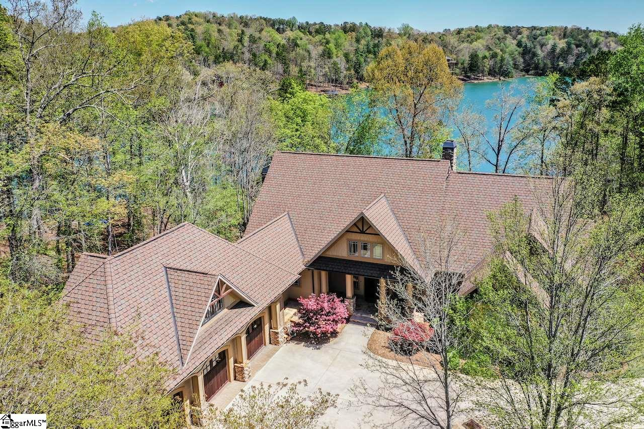 This Lake Keowee waterfront retreat is a must see.  Soaring wood and beam ceilings in the Great Room are complimented by an exquisite wall of windows framing Lake Keowee in your back yard.  This home is meant to be your sanctuary. Nestled in a large bay protected from the main-channel, this home is rustic-casual architecture. The spacious open floor plan features multiple fireplaces located in The Great Room on the main floor as well as on the titled covered porch accessed by sliding glass doors from the Dining Room. Wood floors throughout the main level with tiled bathrooms.  The Master bedroom has floor to ceiling transom windows facing Lake Keowee and its own private balcony. A spacious alcove with triple windows is perfect for your home office desk. Naturally, there is a jetted tub and walk-in shower as well as a spacious walk-in closet completing the Master Suite.   The gorgeous, bright kitchen features custom granite and cabinets with glass doors for exhibiting your dishes.  A prep sink has its own counter space and convenient cabinets.  You will enjoy the enormous walk-in pantry and the convenient work desk. The powder room is off the Great room and the laundry room adjoins the kitchen and leads into the 3-car attached garage.  Extensive molding, wood floors, wood ceilings, and wood paneling are found in many of the rooms.  It is important to note that there are wonderful views from many rooms in the house. The bonus room over the 3-car garage is the perfect bunk room and it has its own full bath. The terrace level recreation room is tiled.  This room will accommodate your large gatherings! Games of pool and ping-pong can take place simultaneously while other guests enjoy watching the big game.  The built-in entertainment area will accommodate all of your electronics to enjoy music and your TV.  Entertaining would not be complete without a wet-bar with the same granite counters that are on the entertainment center cabinets.  A third fireplace adds ambiance to
