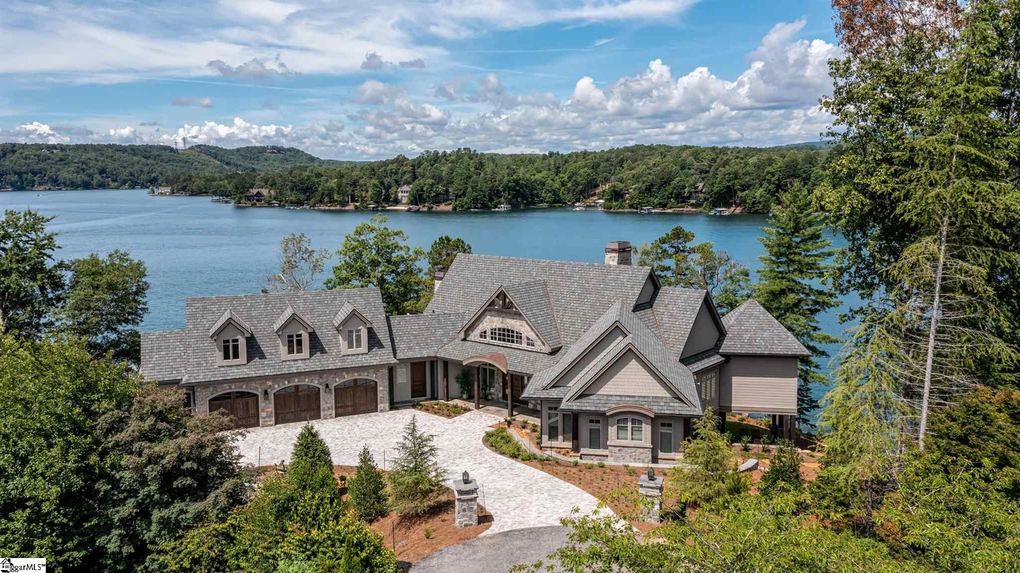 Welcome to 215 Passion Flower Way sitting upon one of the finest lots with premiere views in the Cliffs at Keowee Vineyards.   Unique offering of a fully furnished new home constructed by Fairview Builders and tastefully decorated by Villa Verona Design.  Completed Spring 2021, this 6700 sqft, 5-bedroom home is meticulously landscaped, furnished, and decorated awaiting immediate occupancy to enjoy the season.  Sitting upon a perfect peninsula point lot with very gentle slope and almost 400' of 270-degree expansive panoramic views of waterfront, mountains and sunsets. With a 14-foot-wide entrance driveway and a large paver motor court welcoming you to the front door, upon entry you are immediately captivated with stunning water and mountain views showcasing this incredible lot.  A large open living area with cathedral beamed ceilings over old-world Siberian Oak scraped floors and separate large dining area flank a fully equipped gourmet kitchen and flows through disappearing doors to an inviting screened porch with wood burning fireplace and wrap-around balcony perfect for outdoor living and entertaining.   The attractive kitchen with views of the lake features beautiful honed (leathered) granite counter tops, custom display cabinetry, Sub Zero and Thermador appliances, and ample storage with pull out drawers.  Adjoining the large living area is a beautiful custom wine room behind glass window display, with iron gate doors, stone walls, handcrafted wine barrel ceiling, and beautiful hammered copper sink and leathered granite counter tasting area. A unique floor plan provides 3-bedroom suites on the main level.  The large and relaxing master suite along with 2 guest suites providing welcoming and easy access for your guests.  Convenient just off the living room the master suite and accompanying sitting room/library anchors the right rear corner of the home providing floor to ceiling windows equipped with remote controlled blinds for wonderful panoramic views.  This ma
