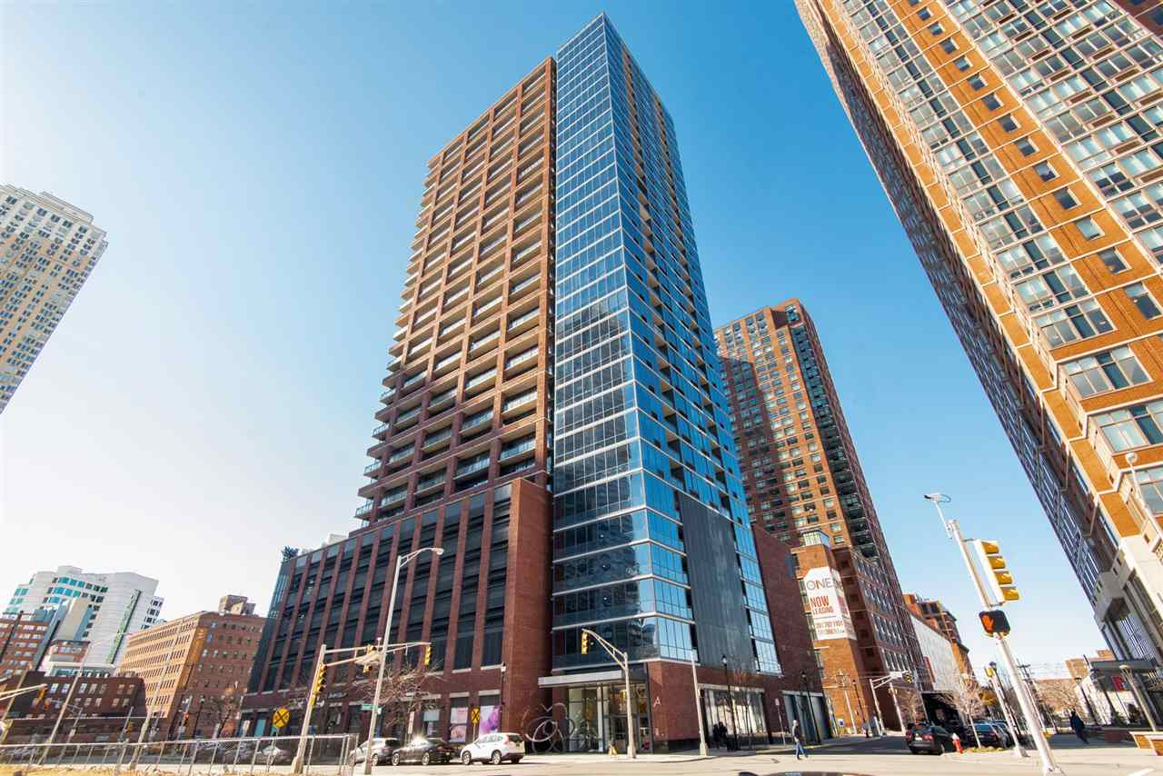 "Beautiful one bedroom located at The ""A"" Condo with New York City View. This unit features wood flooring, private balcony, floor to ceiling windows, designer bathrooms with marble countertops, granite kitchen countertops, 24/7 concierge, package check, beautifully designed lobby, walking distance to the Path Train Stations and steps to Harsimus Cove Light Rail and ferry. PS 16 school district is a plus. Parking is included."