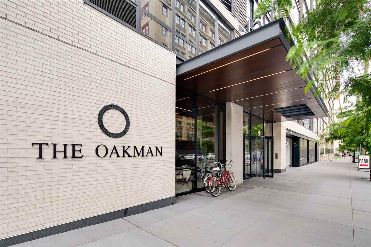 """South facing, corner unit at Jersey City's newest building, The Oakman.  Only a couple of years young, this unit has very high end fixtures and finishes including 5"""" wide oak floors.  The unit will get lots of natural sunlight all year long with unobstructed southern exposure.  High end amenities include full time doorman, gym, playroom, roof top lounge with outdoor swimming pool, and grilling area.  Centrally located a few blocks from Grove Street PATH, the Oakman makes for an easy commute.  Near pedestrian-only Newark Avenue with lots of shopping, dining, and nightlife options.   Best of all the Oakman has a 20 year tax abatement until 2036 with the current tax rate of under 1%!"""