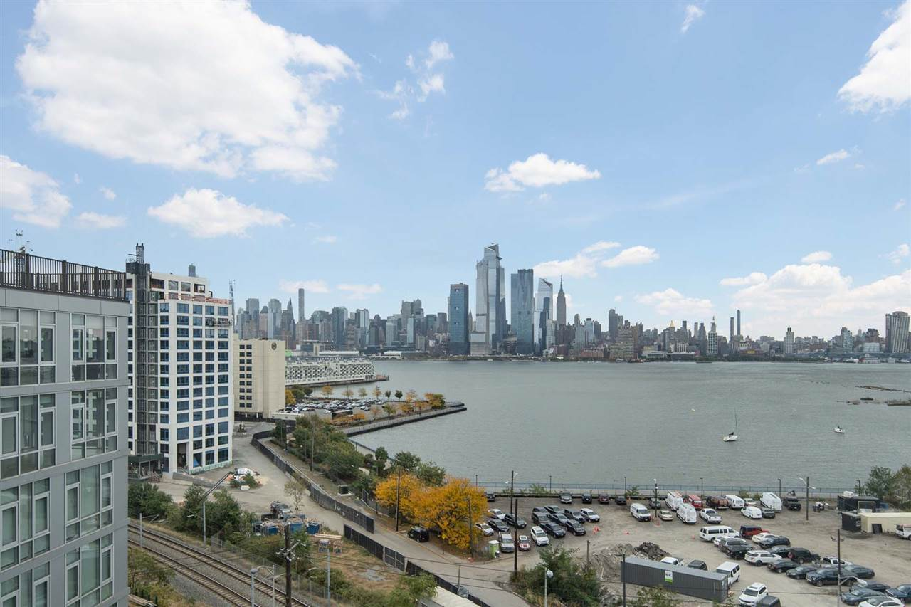 """Landlord Pays Broker Fee.  Modern Luxury Waterfront building is located in the heart of Weehawken and Hoboken border with breathtaking NYC views.  2 Bedroom 2 Full Bath rental includes 1 covered indoor gargage parking space at """"Gateway"""".  Spacious living room/dining area has floor to ceiling windows with direct views of NYC and Hudson River from the Top floor. Upscale kitchen with granite counters & stainless steel appliances.  Washer and dryer in the unit, generous closet space, hardwood and tiled floors. Central heat and air conditioning.  24 hour concierge and 24 hour on-site management. Additional building amenities include gym, business center, community room with flat screen TV, Large outdoor deck with Infinity pool overlooking the Manhattan skyline, bike storage and shuttle to PATH. Guest parking available. Walking distance to the Ferry, Light Rail and NYC Bus and Uptown Hoboken bars and nightlife. Pet friendly building."""