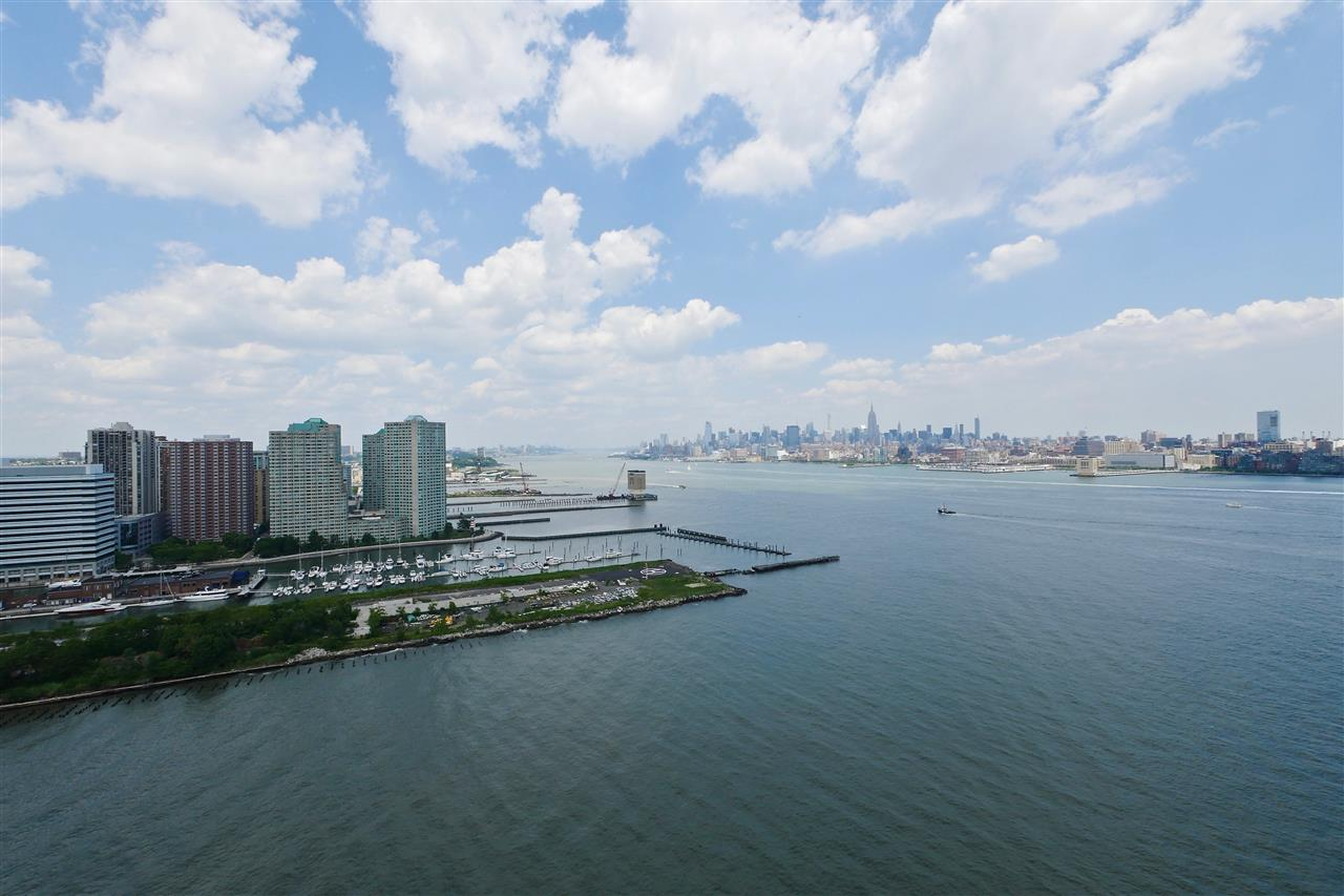 Welcome yourself to this waterfront unit with gorgeous views of Midtown Manhattan and beyond. Enjoy a wall of windows looking out to the Hudson River, all the way up to the George Washington Bridge, or some outdoor time on your private terrace while marveling at the amazing colors in the sky from the evening sunset. This Northwest corner unit further features ultra sleek Kitchen & Bathrooms with imported finishes throughout, plus gleaming hardwood floors, laundry in unit & valet parking. Light Rail, PATH & ferry all in close proximity. Building features 24-hr concierge, pool, fitness room, community rm, kids play area & much more! One month broker fee.