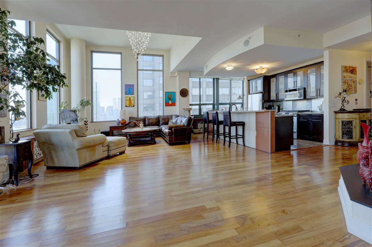 Rarely available Penthouse condo with NYC & Hudson River views. This stunning 2 bedroom plus Den and 2.5 bath,  apt is bright and spacious with lots of windows,  high ceilings (14ft) and a welcoming open floor plan. This unit is approx.1900 sq ft and has a unique & modern design with many custom wardrobes and upgrades. Washer/dryer in unit.  Conveniently located one block away from the Exchange Place PATH, Hudson Light rail and NY Waterway Ferries to Manhattan.  Jersey City's. waterfront is one of the city's best locations to call home.  This is a full amenity luxury building with 24 hour doorman, 5th flr community lounge, 6th flr gym and Rooftop lounge equipped with BBQ station, lounge chairs, tables, benches and dramatic views. Parking available for an additional fee. Bicycle storage available in building.