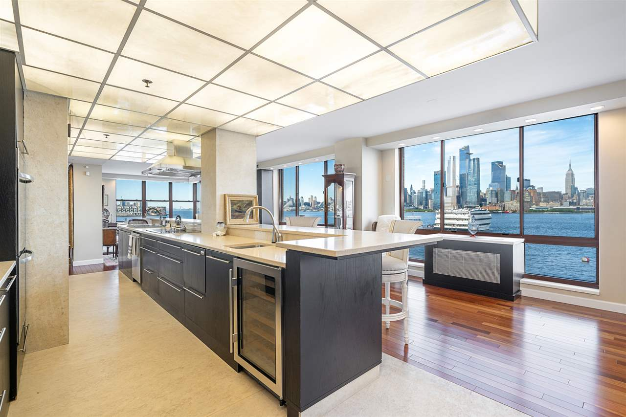 Introducing a truly singular residence of the highest caliber.  The coveted, east-facing, 'twin-corner' unit at Constitution Court with the largest private outdoor space in the community.  An absolute treasure on the Hoboken waterfront, this 2500sf 3 bed + den, 2.5 bath home enjoys southern, eastern and northern exposure via 20 oversized windows. Your expansive great-room wraps the northeast corner of the home offering ample room for formal dining in addition to generous living space.  Live each day with one of the world's most dynamic works of  art… an unparalleled, 270° view of New York City and the majestic Hudson River... Effortlessly host large gatherings beneath a backlit, glass-tile ceiling at one of the longest granite bars on the left bank… Your 20' kitchen is built to thrill with limestone floors, double-height granite counters and custom cabinetry. Sub-Zero and Miele appliance package includes a fully integrated coffee and wine preservation systems. Grill, relax and unwind on your expansive terrace complete with weather-proof TV and speakers, both connected to your Smart Home Media System. Master suite 'north' offers 7'x8' walk-in closet and the most indulgent of en suite baths:  Radiant floors, hydrotherapy shower heads, deep soaking tub, Duravit and Porcelanosa fixtures. Master suite 'south' has another en suite bath and more great closet space. The homes' southeast corner can be closed off behind elegant, twin sliding doors to create an office / den / media room or leave it open for still more living space. Third bedroom faces south and is across from your formal laundry room complete with elevated dog grooming 'bath', custom closets, 2 washers and 2 dryers. All this plus cherry hardwood floors, fully motorized blinds, a walk-in coat closet and a separate pantry. 'The Shipyard Community' offers you multiple gyms, a gorgeous rooftop residents' lounge, two pools, 24-hr concierge and available rental parking for multiple cars. Your location is ideal: Next