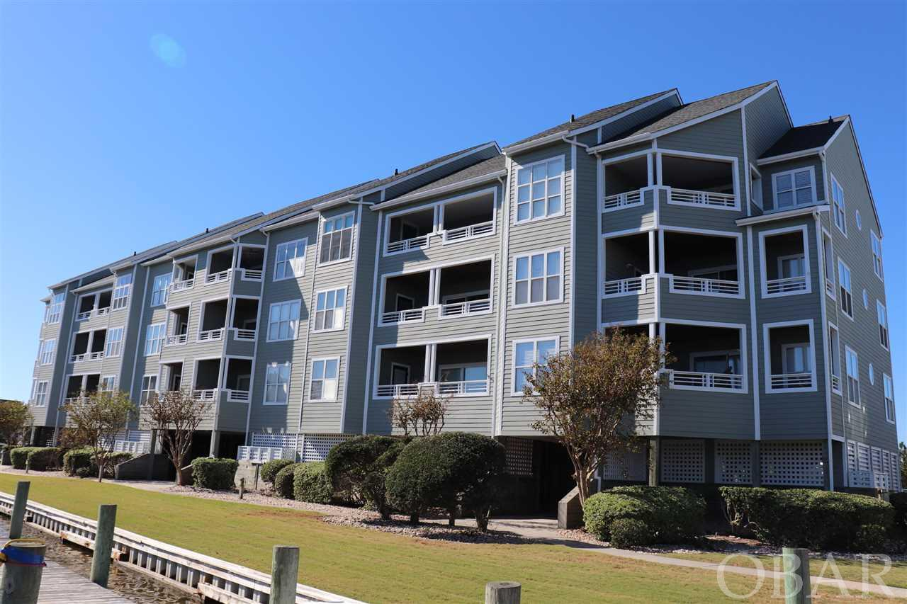 """Top Floor 2 Bedroom, 2 Bath furnished condo, vaulted ceilings, fireplace with a elevator and amazing views in the Outer Banks premier boaters community of Pirates Cove - Buccaneer Village. Open living area with Sound and canal views greet you when you walk in the door. Clear panoramic views from bedrooms. A spacious deck allows for enjoying outdoor breezes. Large storage ground floor lockup for all your beach toys. This home has been very lightly used.  A qualified boat owning buyer will have rights to a 35 ft boat dock slip for $130 a year. More than just a home, Pirates Cove is a lifestyle. """"Fishing, fun and friends"""". Enjoy access to world class fishing and water sports. Association amenities include swimming pools, clubhouse, fire pit, volleyball, basketball, pavilion picnicking shelter, fitness center, marina that has over 4 miles of docks that are fantastic for walking or running, or just kick back and watch the boats come in from your deck or relaxing at the marina restaurant. Don't have a boat? No problem charter or walk just under the bridge to the NC Wildlife water access including fishing pier, boat ramp and multiple launch sites for small craft kayaks etc. This home allows for quiet enjoyment, while being walking distance to the fun.  New HVAC 2017 with WIFI thermostat 2018 and water heater in 2017 new LVT flooring 2020.  Have extra guest?  The living room sofa is a pull out and sleeps two comfortably."""