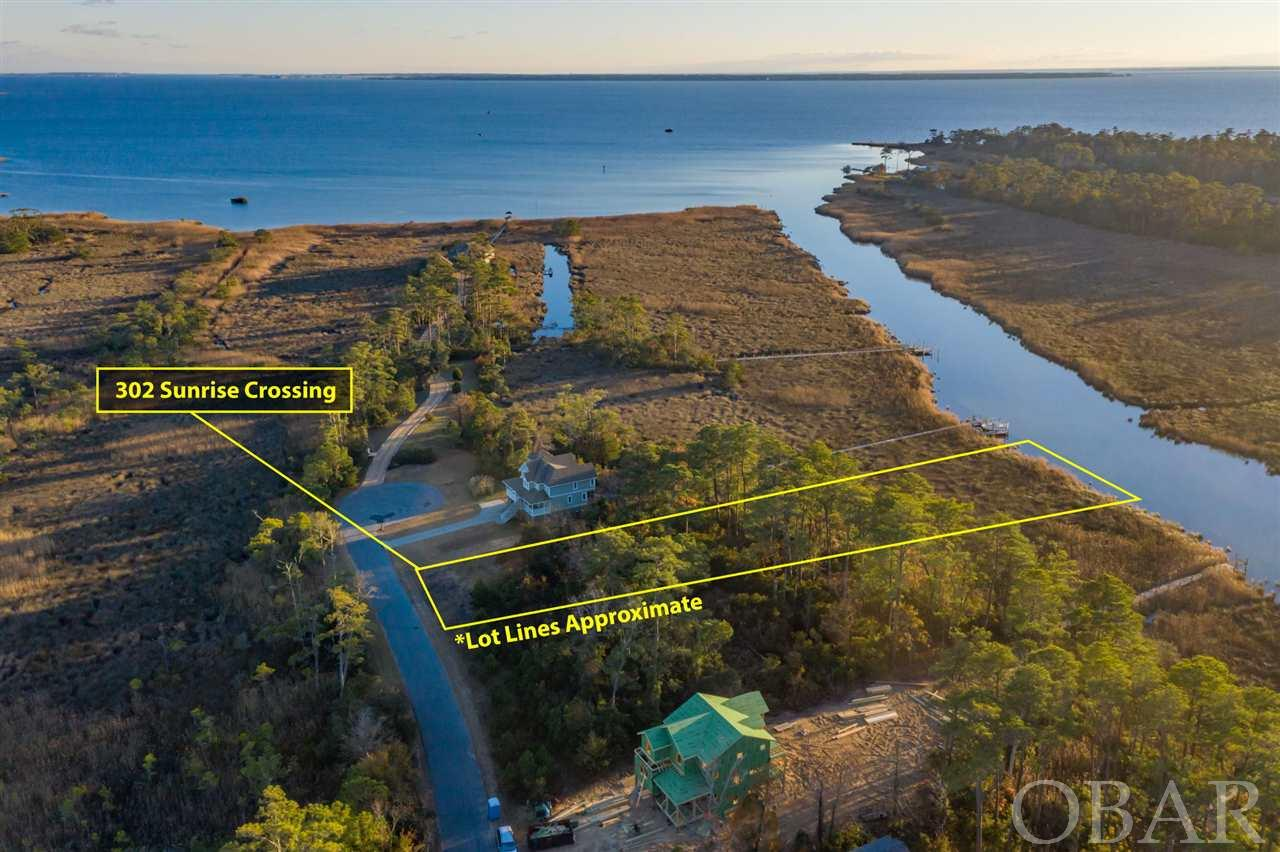 One of the most beautiful large building lots located in Sunrise Crossing.  This property features beautiful sunset, canal, and sound views. Build your own dock or Sunrise Crossing offers a community boardwalk and dock to provide sound access. Perfect for kayaking or world class fishing and crabbing.  Build your custom dream home and enjoy all the OBX has to offer.