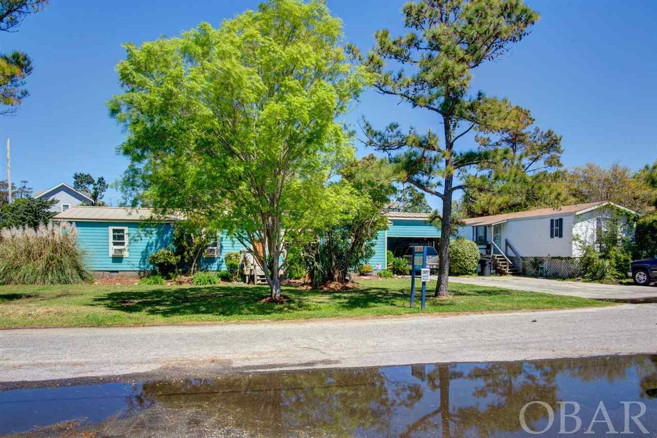 Whether you are looking for a year round residence, short term/long term rental,  or a second home, this is a great opportunity to secure a home for under $300K on Hatteras Island! This listing offers NOT only ONE home with established long term rental income but TWO! Both homes are well-maintained and located in a quiet neighborhood with landscaped front and private extra large back yard. First home offers 3 bedrooms, one master suite with a master bath and two comfortable size bedrooms that share a full bath. Perfect fit for a single family. It's nice size kitchen with stainless steel appliances, island with built-in bar, laminate counter tops, and plentiful cabinet space is a Chef's dream. The screened-in back patio with a waterproof rubber roof is an awesome space for entertaining or family gatherings. The utility room off of the kitchen includes a full size, side-by-side washer and dryer and easy access to the carport/work room. You will feel right at home nestled in front of the fireplace on a chilly night in the spacious den, head to the office to wrap up your work day, or relax in the living room with a good book. The living and dining room have bottom down top up cellular shades. Need extra storage or additional workspace? Don't worry...The carport has a extend utility room for your extra hobbies. This is a great place to call home! The second home is a Oakwood single wide mobile home (80x14) built in 1997 with 3 bedrooms, 2 full baths, spacious living area and a full size kitchen. This a great starter home.  You hit the jack pot...opportunities at this price point do not come along every day...Don't miss this hidden gem, it won't last!