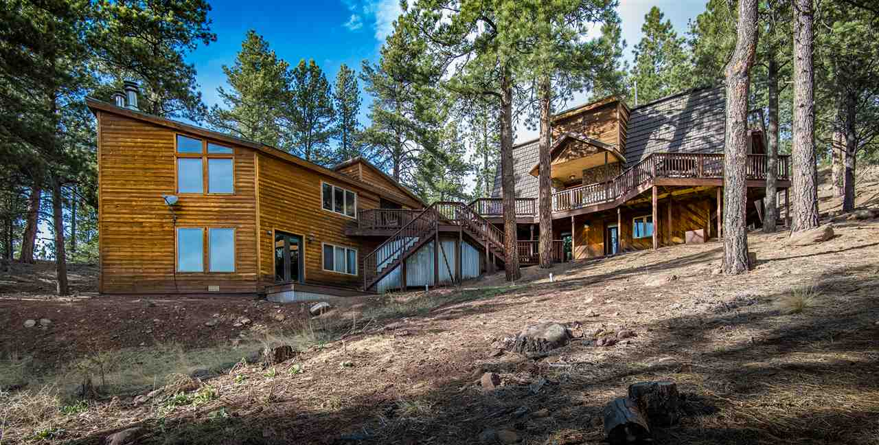 The perfect retreat less than a half of mile to the base of the ski area and less than a mile to downtown Angel Fire, views of the Angel Fire Resort Golf Course! This retreat has endless potential with approximately a total of 4100 sqft of heated living space. Main house has approximately 2118 sqft. with 5 bedrooms, 5 baths with master suite fireplace, galley style kitchen and dining, cozy living area with fireplace. Two private guest studios have two fireplaces with open concept kitchen, dining, living and master suite with spacious bath. 4 combined lots to give 3.7 acres to play on. Think outside the box with this retreat!