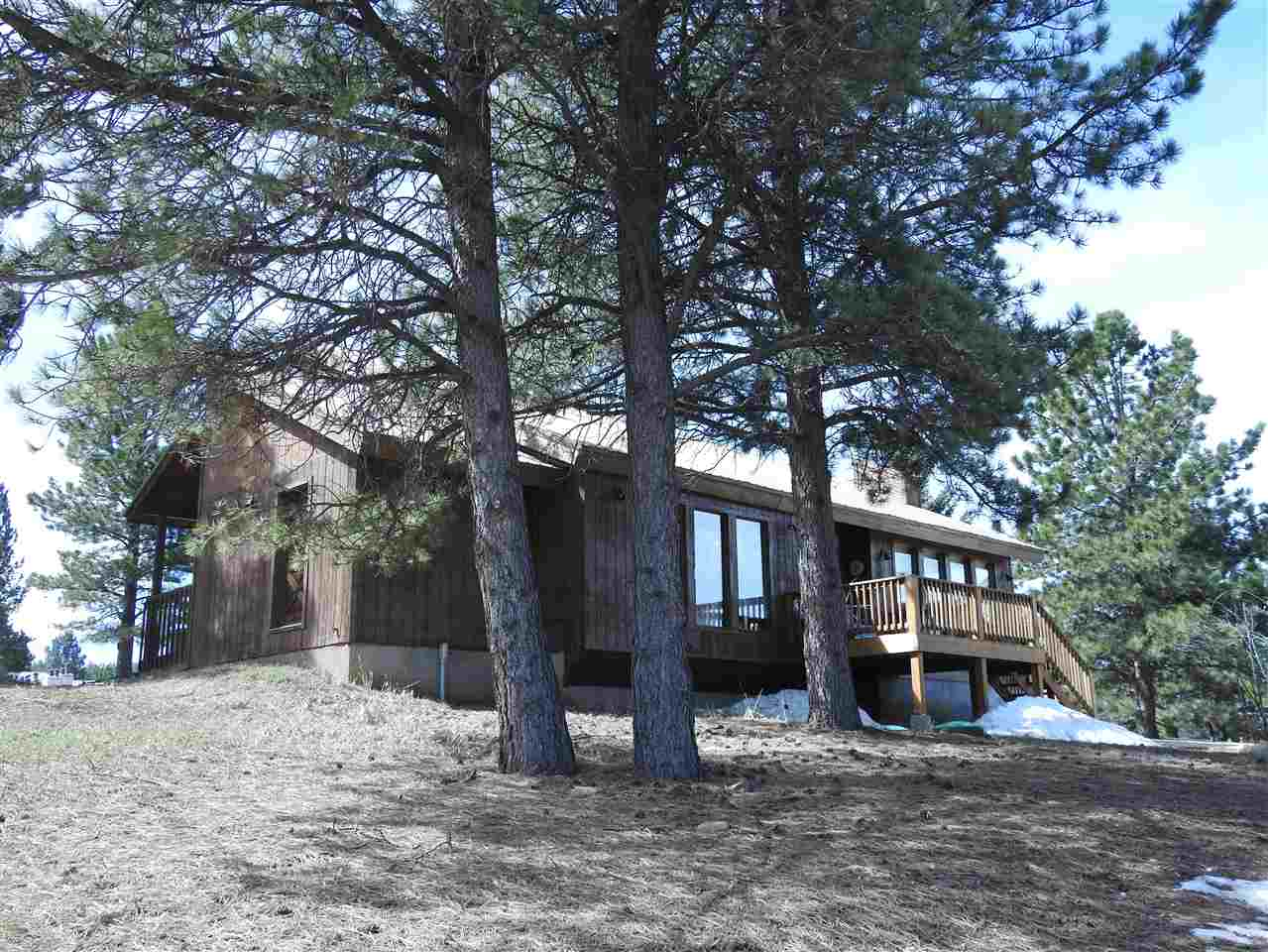 Located just a couple blocks from Angel Fire Ski Resort this house sits perched up on a hill with a mountain view.  Flat and newly graveled road makes for easy access year round.  Access is from both sides of the house.  4 bedrooms, 4 bath and a generous living room with rock fireplace. Large kitchen and dining area to seat the whole family.    Large enough to have multiple families or multi generational families.  Would make a great rental because of location to ski area.