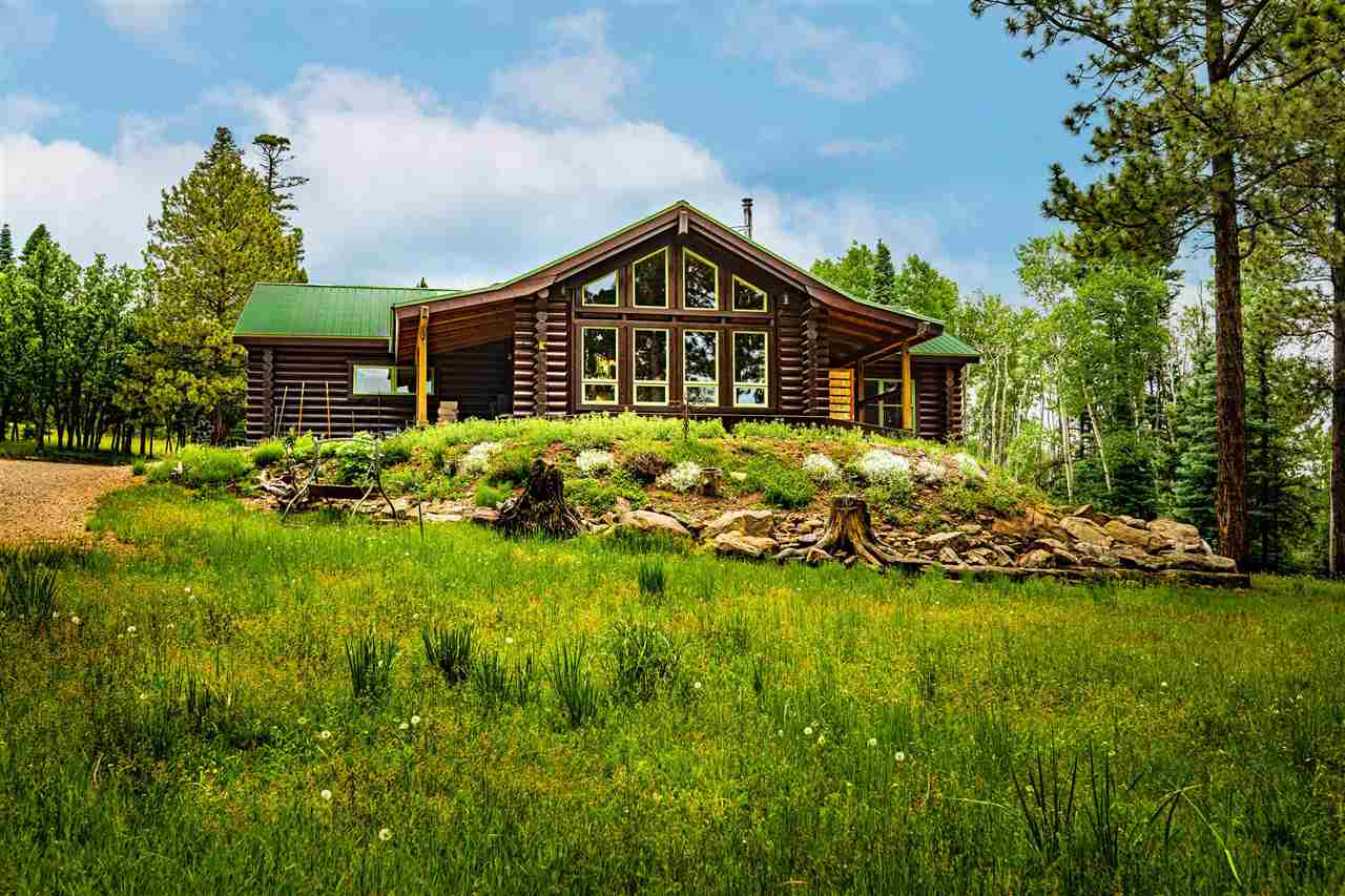 FOR THE ADVENTURER IN LIFE! Set on 33.4 acres with an abundance of wildlife, this property captures true mountain flavor and all just a short distance in to Angel Fire for skiing and golfing.  Log home with approx. 2145 sq. ft. plus a 30x40 heated metal garage and acreage to boot. Pond with windmill sits just in front of the house and well stocked with fish. West boundary of the property borders 1.5 million acres of Carson National Forest. Hiking, snowmobiling or horseback riding is in your back yard.  Home is constructed of 10 inch logs and sips panel construction with infloor heat.  3 bed 2 bath and all single level living.  Perfect size kitchen for someone who enjoys cooking and baking.  Great living space for those late night poker games.   Come enjoy all this property has to offer.