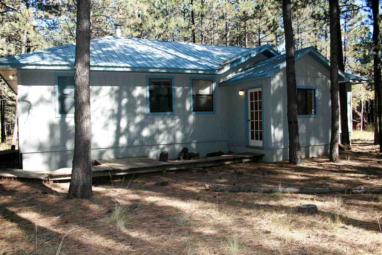 Cozy 3 bedroom, 2 bathroom home with a detached garage. Great price ! Located close to the Country Club and PGA rated golf course. Ski storage in mudroom.  Wood burning stove in main room.  Flat easy lot. Mature trees surround house.  Detached garage perfect for all your mountain toys.