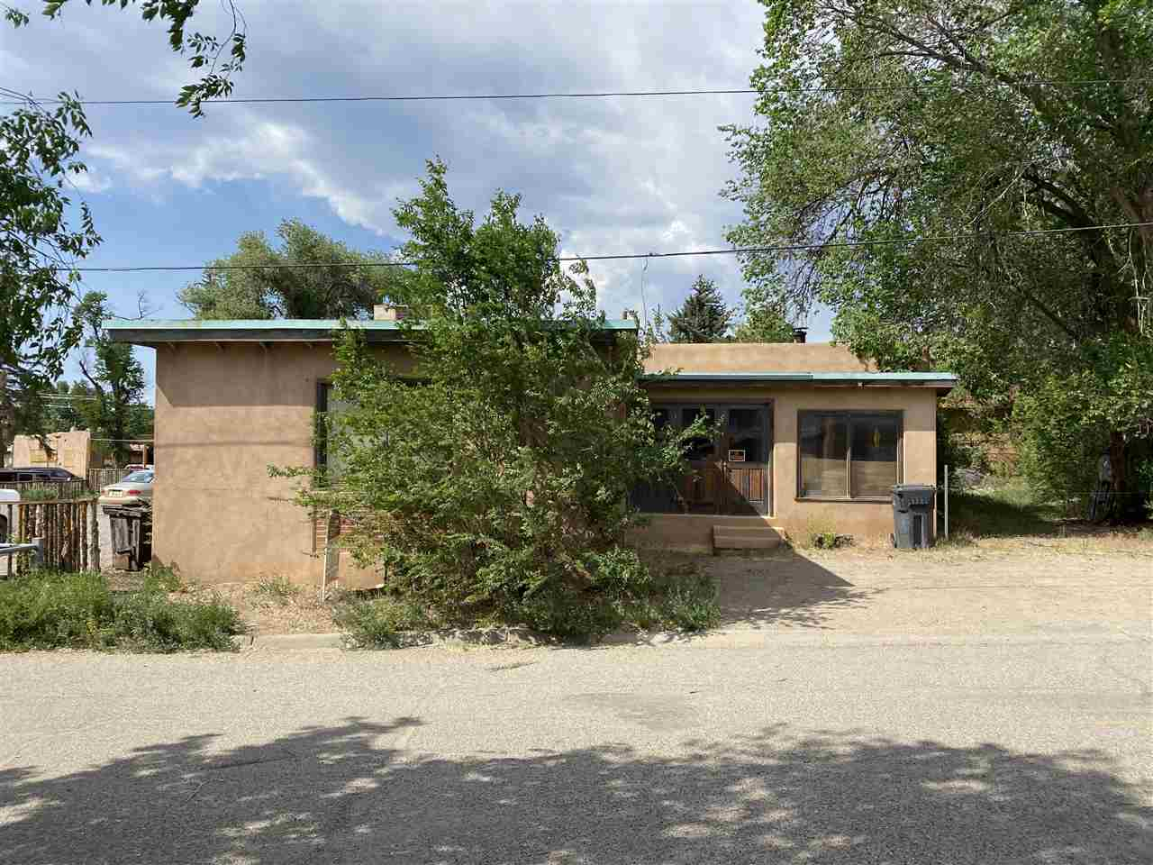 This carpentry shop was built in the early 1930's in the historical district of the Town of Taos and is now ready for its future owner to transform it into something amazing. The main section of this property was built of adobe and vigas, and offers an open floorplan that lends itself to many possibilities. To sweeten the deal, it also has a kitchen, office and half bath. Main section has a woodstove.  Office, kitchen and bathroom are heated with forced air and cooled with an air conditioner. Shop is located right off of Brooks Street, but has land on the east and around the back for building or parking. The location of this property is ideal, and the possibilities are endless. Schedule your showing today!