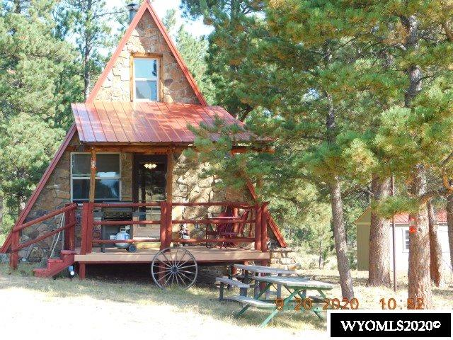 MOUNTAIN CABIN on 5 acres. A-frame with new steel roof, appliances, flooring, electrical, sewer and more.  Secluded among evergreen trees with view to the West toward Laramie Peak.  Take your morning coffee onto the deck 12x16 off living room that is covered.  Also a deck 8x16 off the master bedroom.  The kitchen has all new appliances, new custom cabinets and pantry is custom built. Lots of new items have been added to the home, as well as a new 12x16 storage shed. A nifty mountain cabin that is a must to see. North side of property is joined to BLM acreage, State Land is 2 miles and Forest enthusiast!!  To view, call Shirley at Aspen Realty 307-358-3586